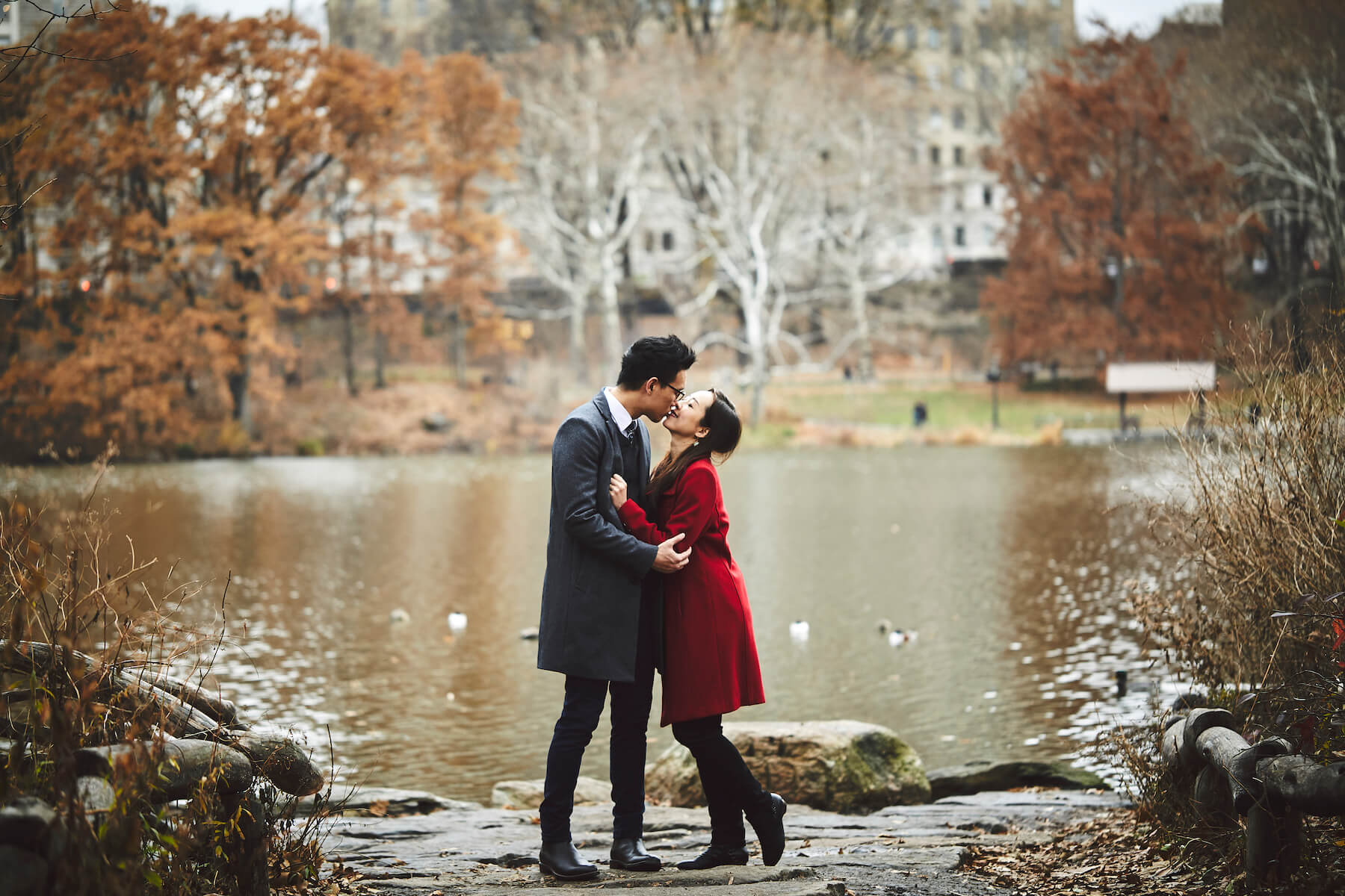 Couple holding each other and kissing in central park, New York City, New York