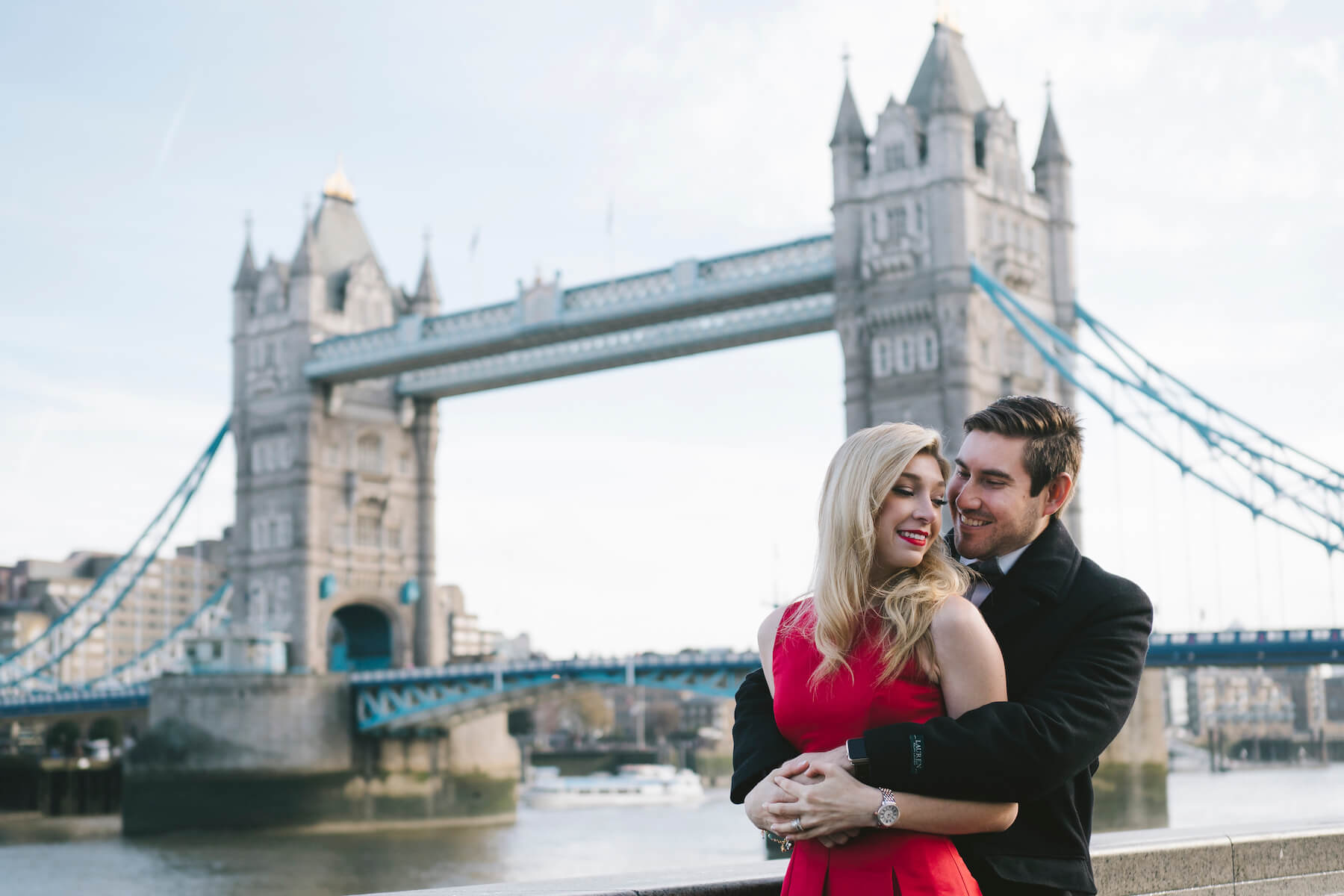 couple sitting and holding each other, dressed up in formal attire in front of the Tower Bridge in London, England