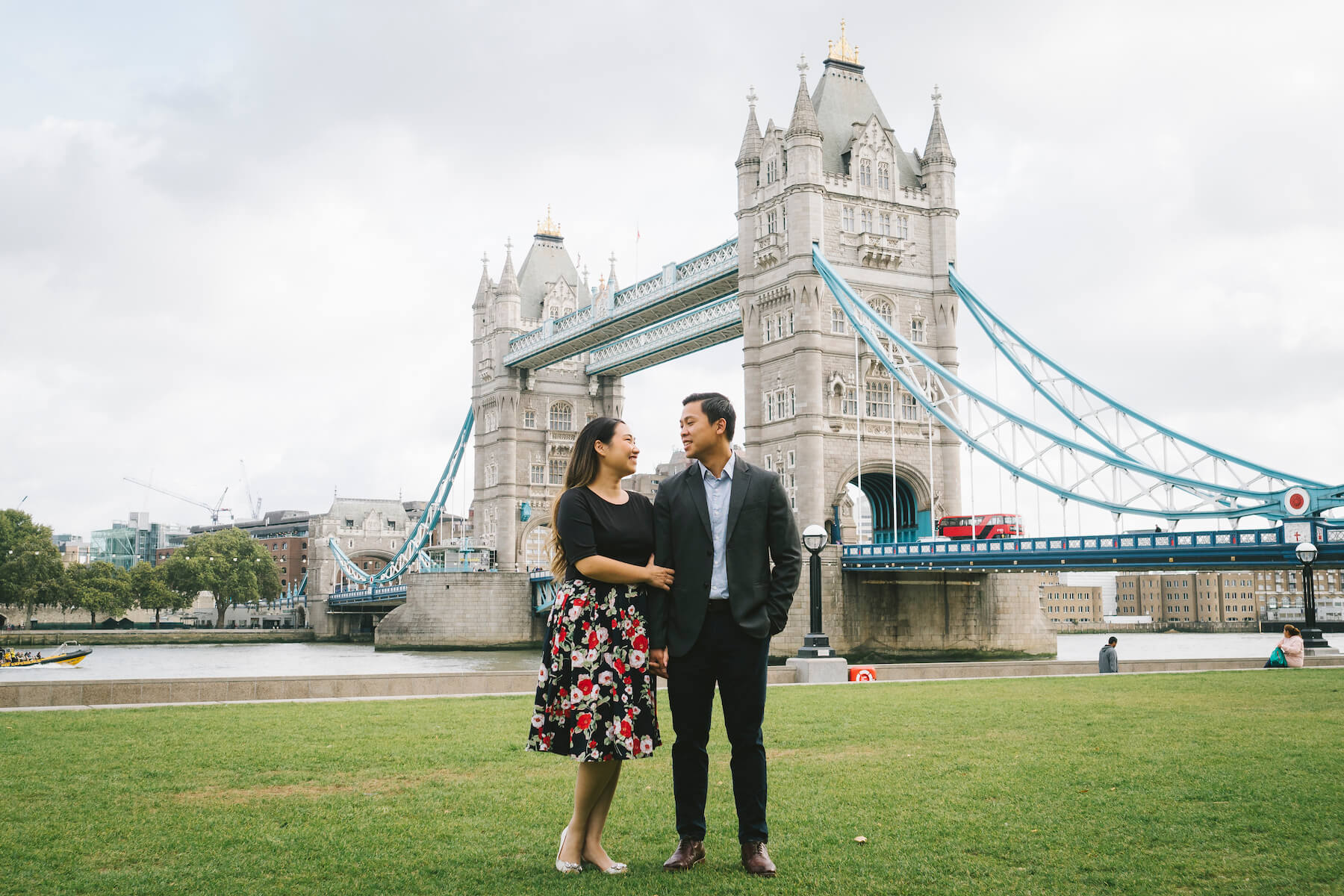 Couple in front of the London Bridge holding hands, London, England
