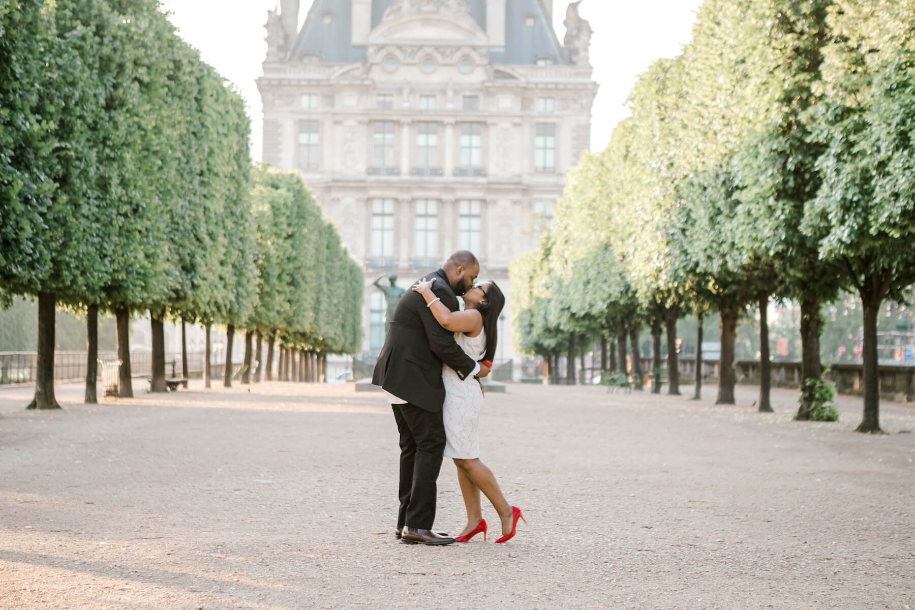 A couple kissing after a wedding proposal in Louvre grounds in Paris, France