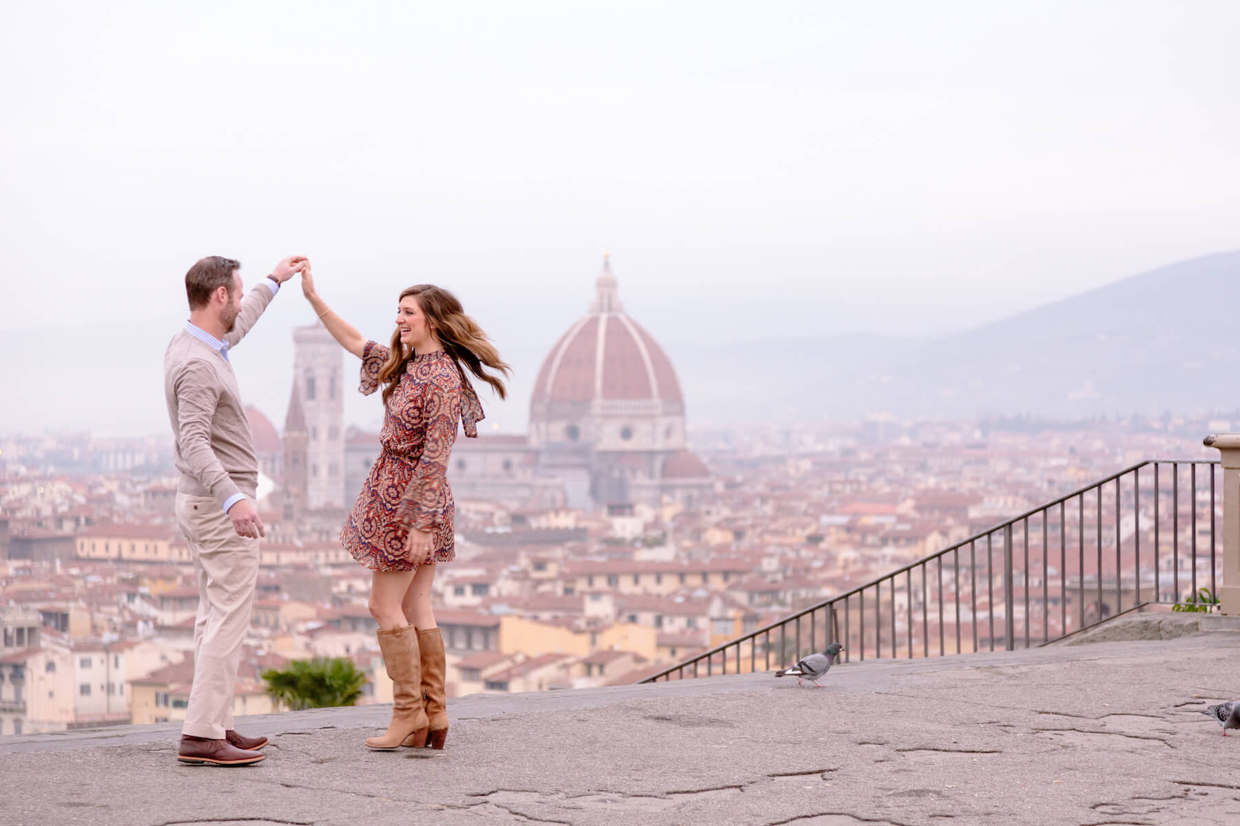Couple dancing on a lookout point, overlooking the city of Florence, Italy