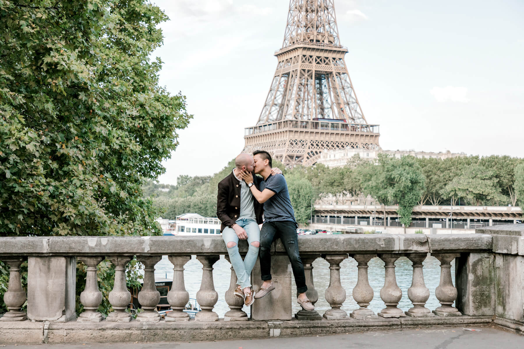 A couple kissing each other in front of the Eiffel Tower in Paris France