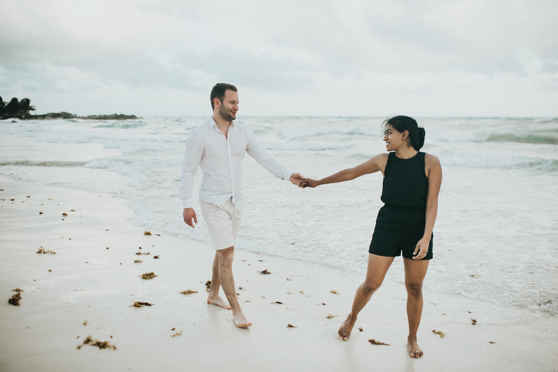 couple holding hands and looking at each other on the beach in Tulum, Mexico
