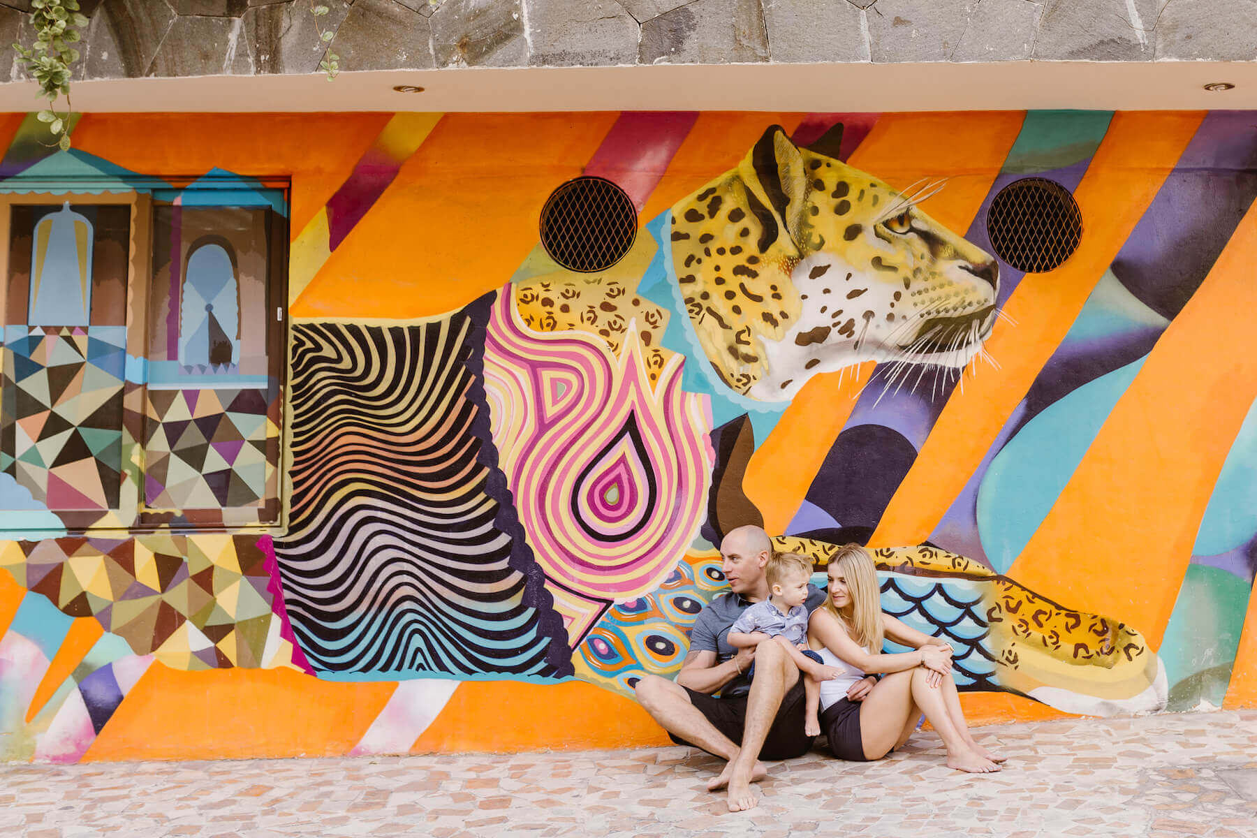 family in sitting down in front of a colourful painted wall in Playa del Carmen, Mexico