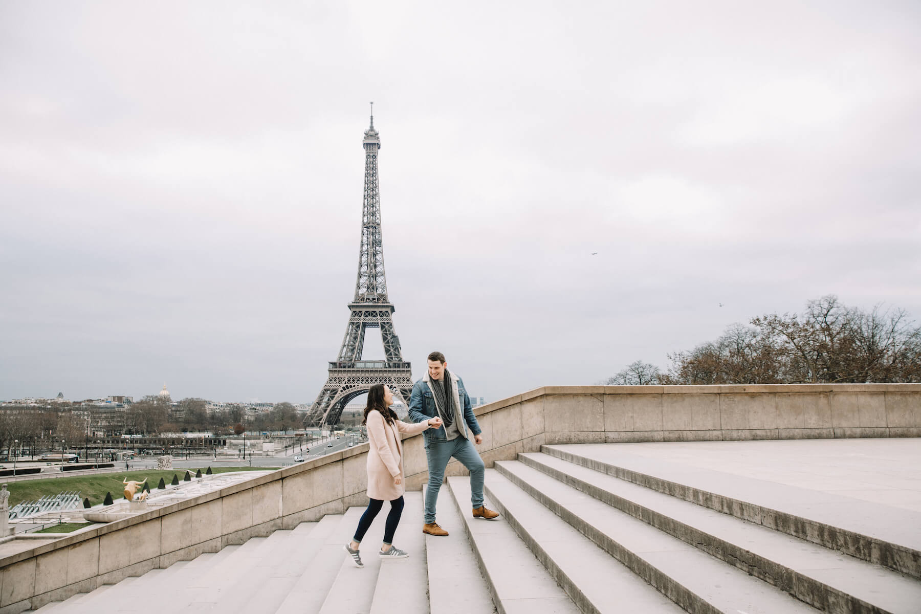 A man walking up stairs with a woman near the Eiffel tower in Paris, France