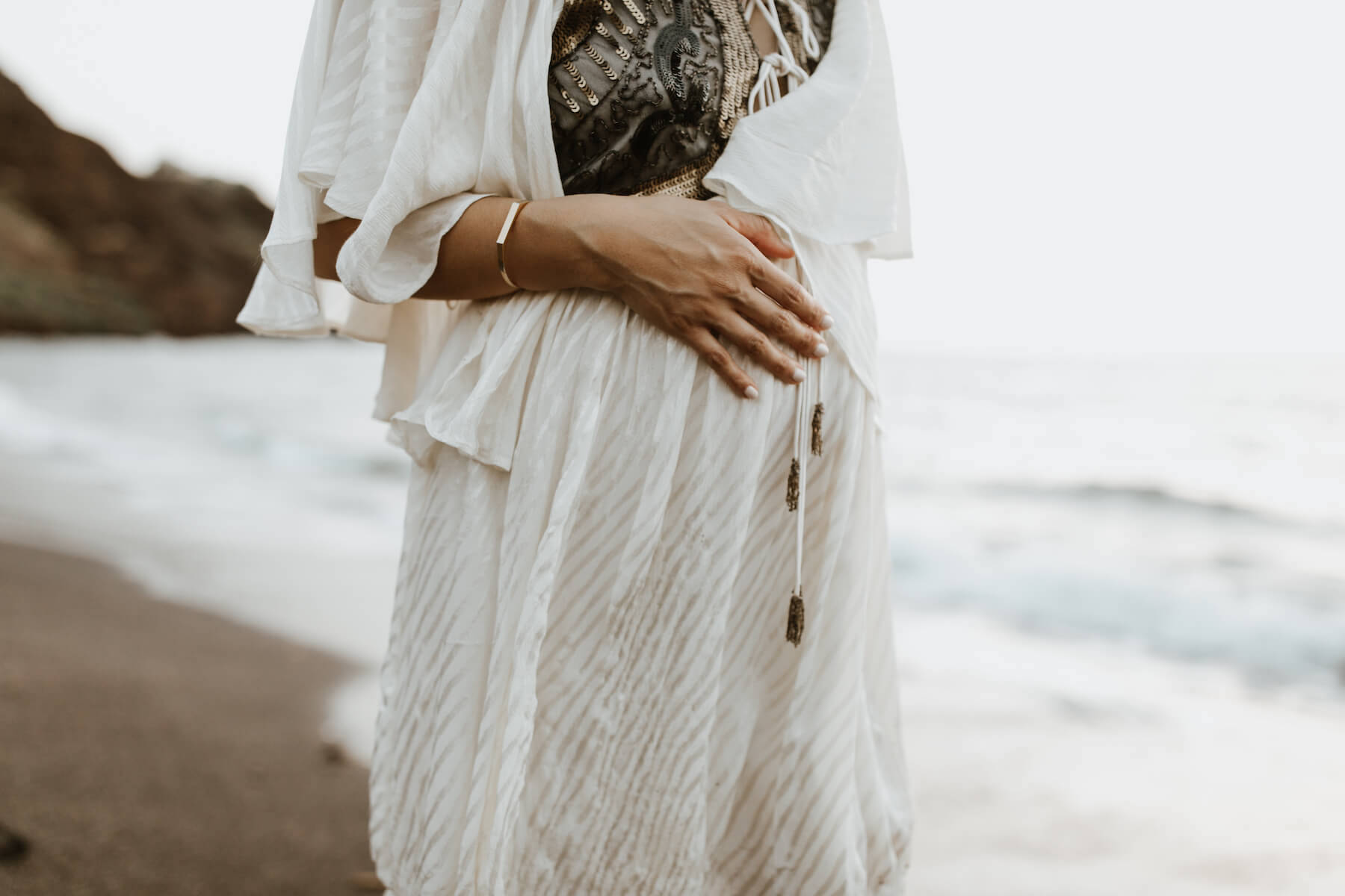 pregnant woman holding her stomach on the beach, wearing beautiful white dress in Maui, Hawaii