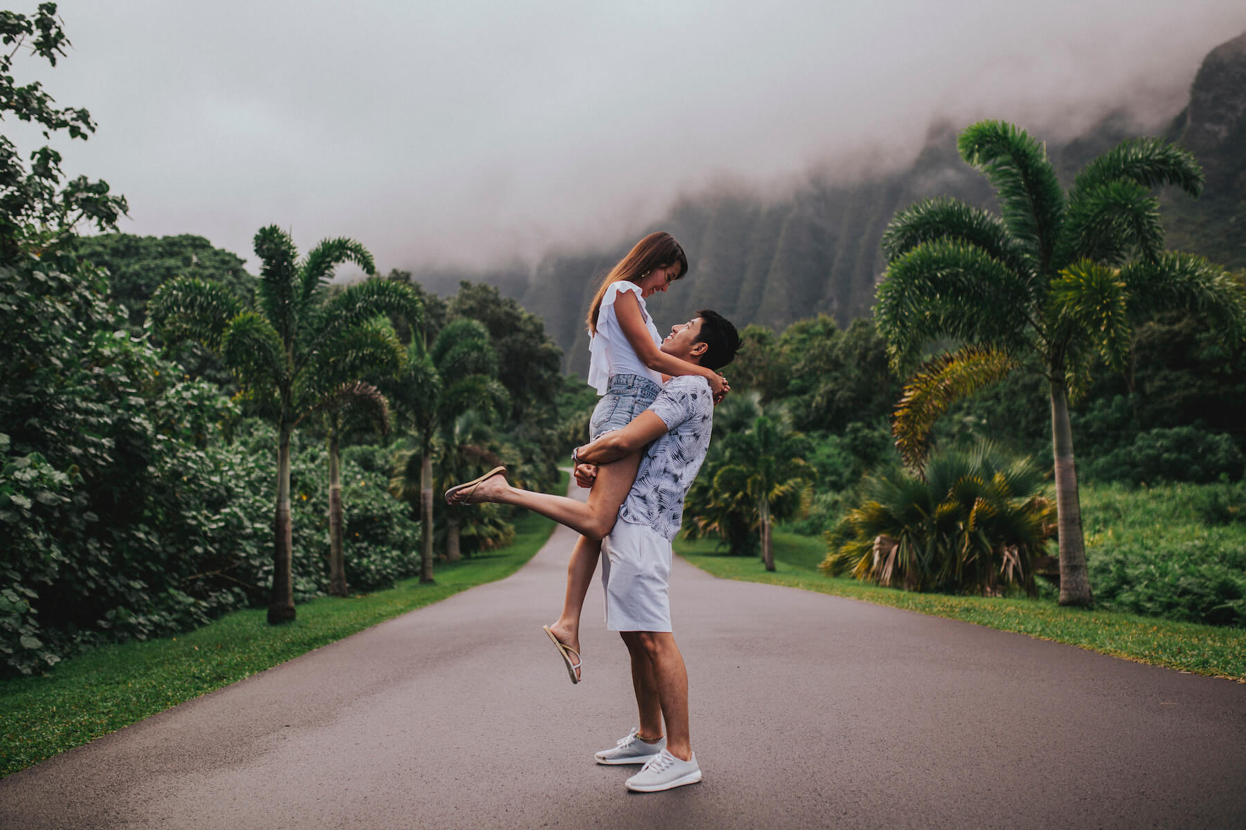 A couple standing in the middle of the road, she is being lifted and they're looking at each other in Honolulu, Hawaii