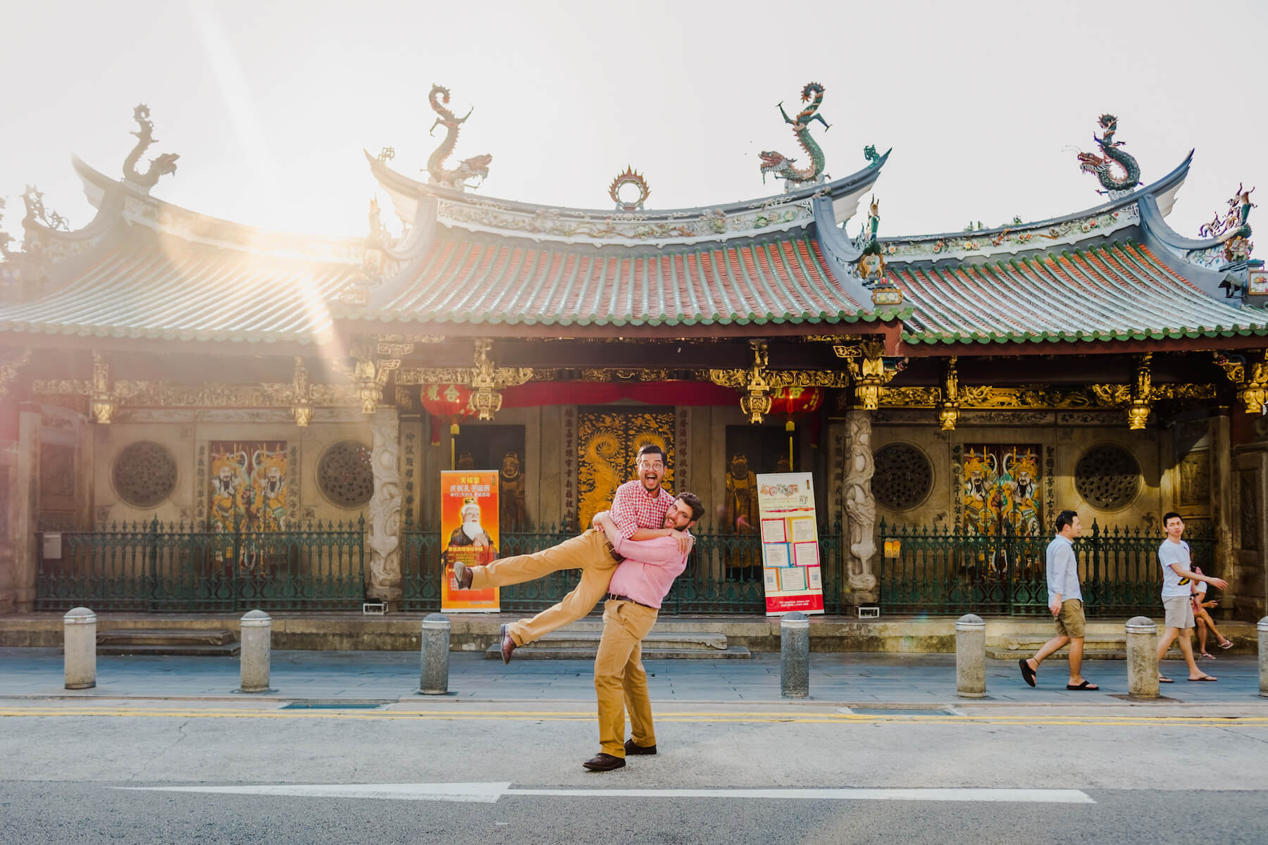 couple in front of a temple, one person is lifting the other person and both are laughing in Singapore, Singapore