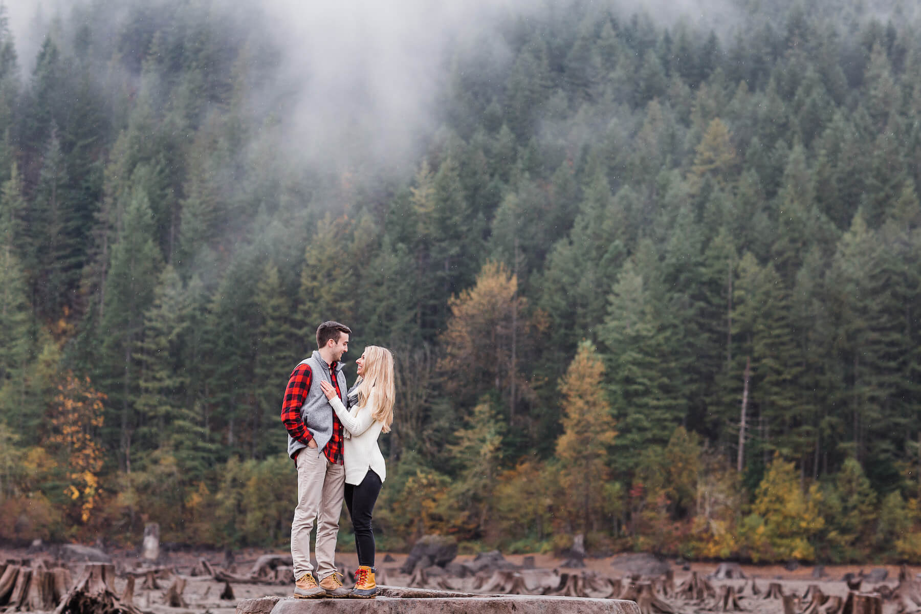 couple embracing at Rattle snake lake, it's foggy and raining in Seattle, Washington