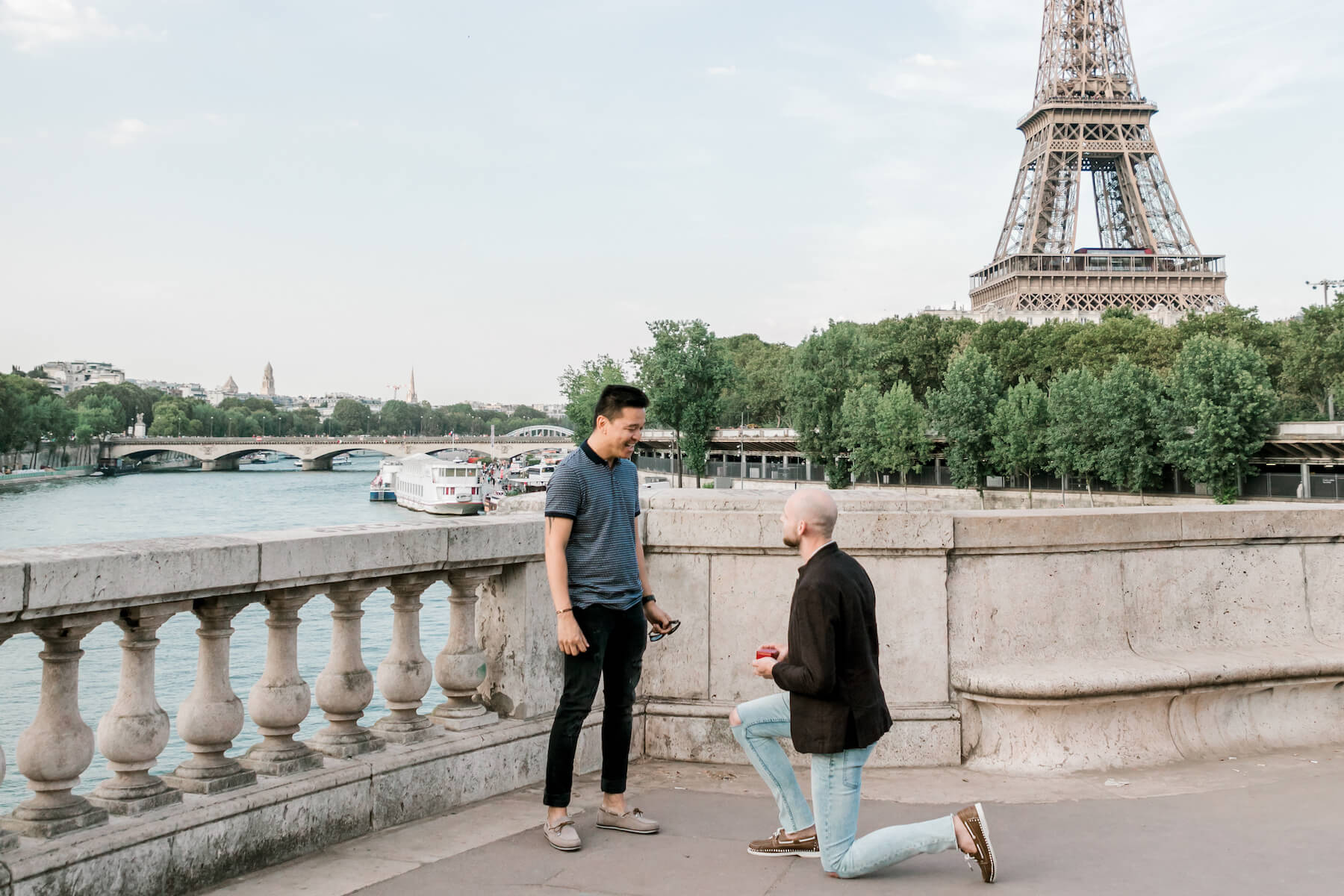 A man proposes on one knee in front of the Eiffel tower in Paris, France