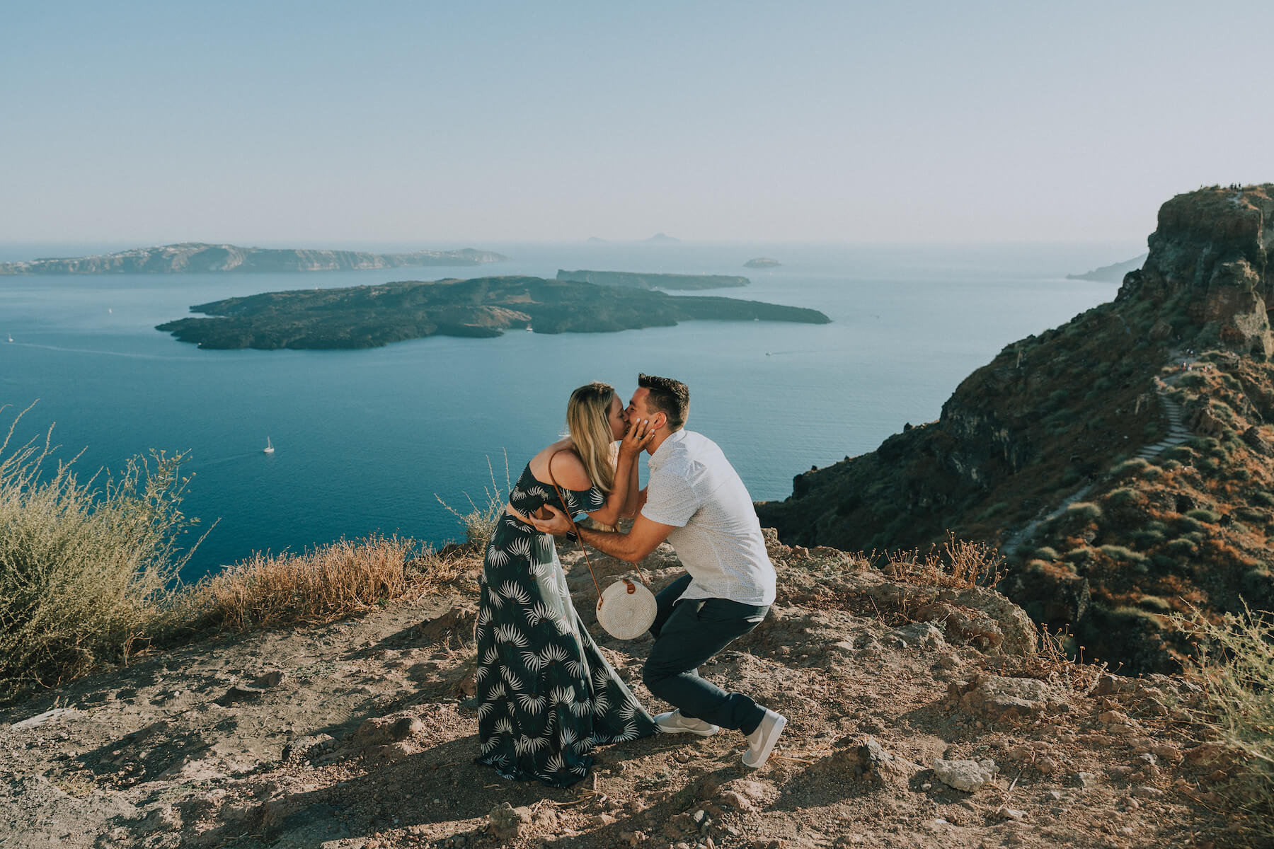 couple in Santorini, the man is proposing and the woman is surprised in Santorini, Greece