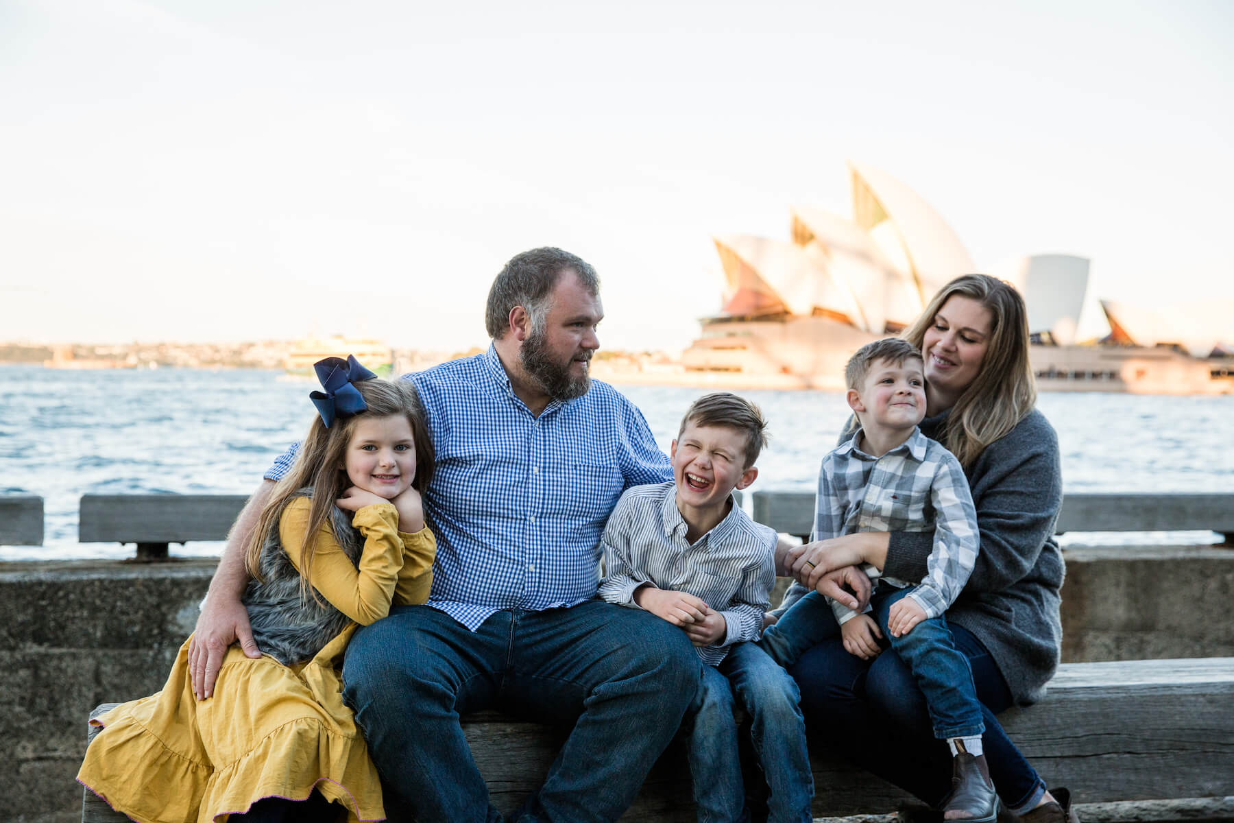 a family of four sitting down with the Opera House behind them in Sydney, Australia