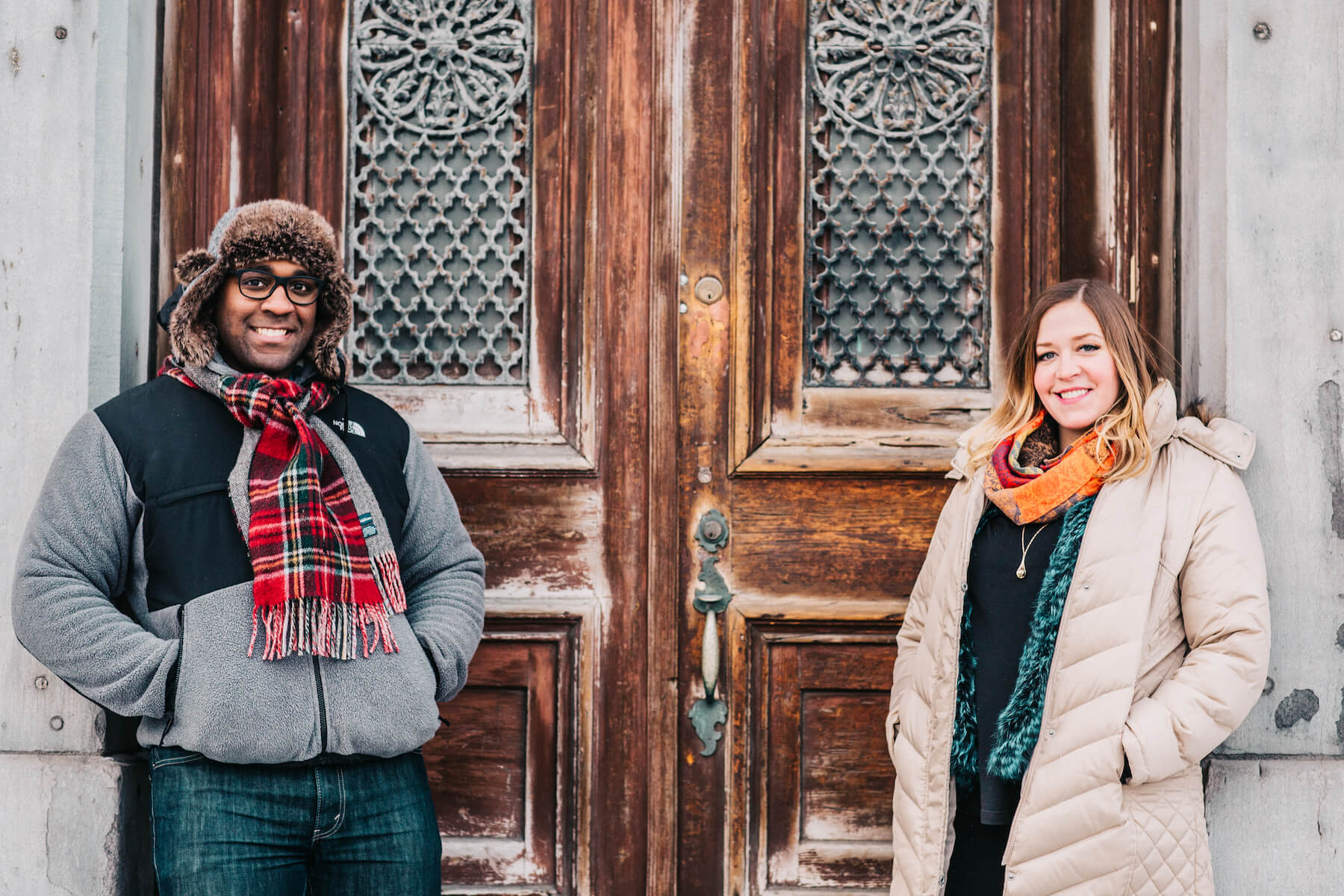 Couple standing in front of an old door in Montreal, Quebec