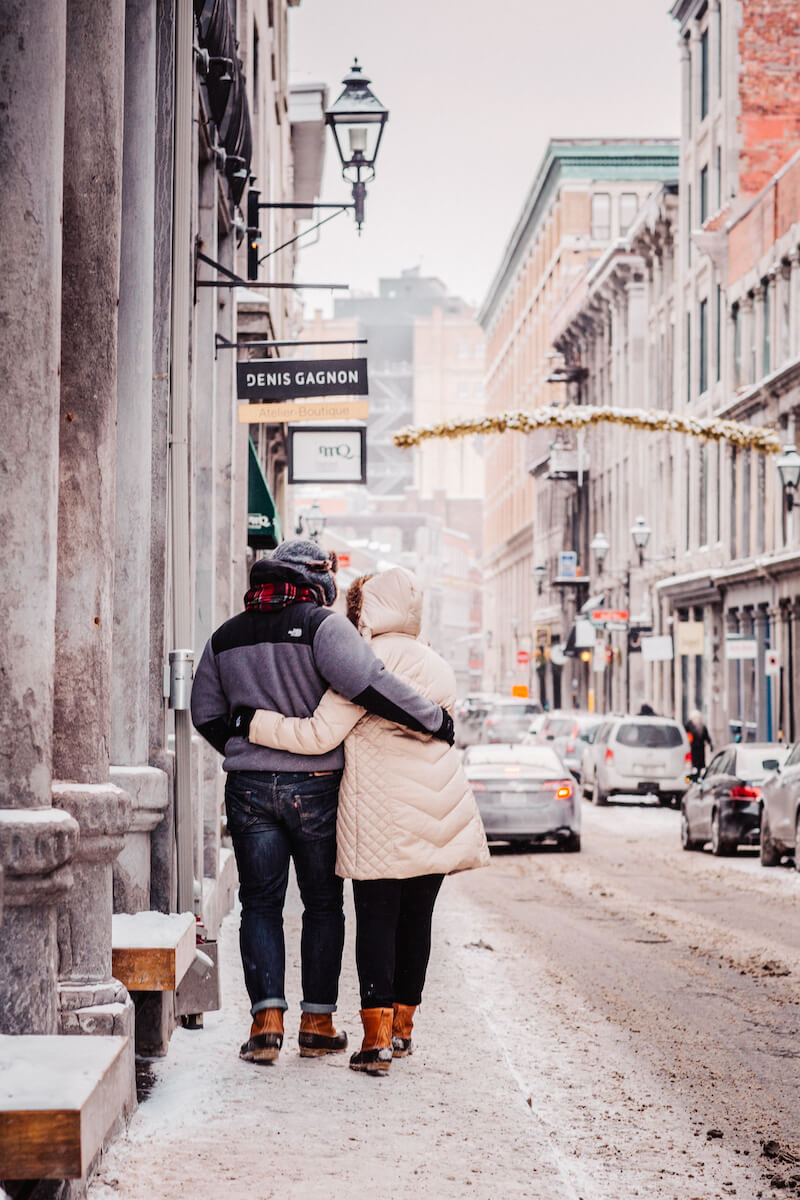 couple holding each other walking down a snowy street in Montreal, Quebec