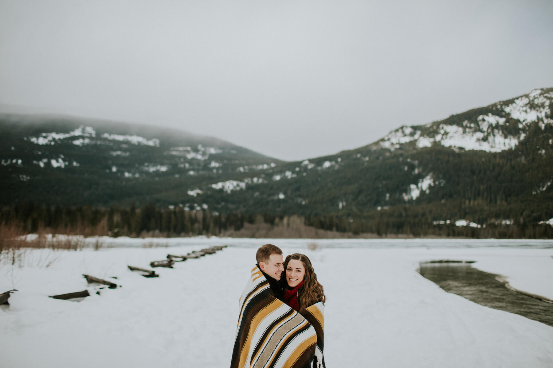 couple hugging and standing in the snow in Whistler, BC, Canada