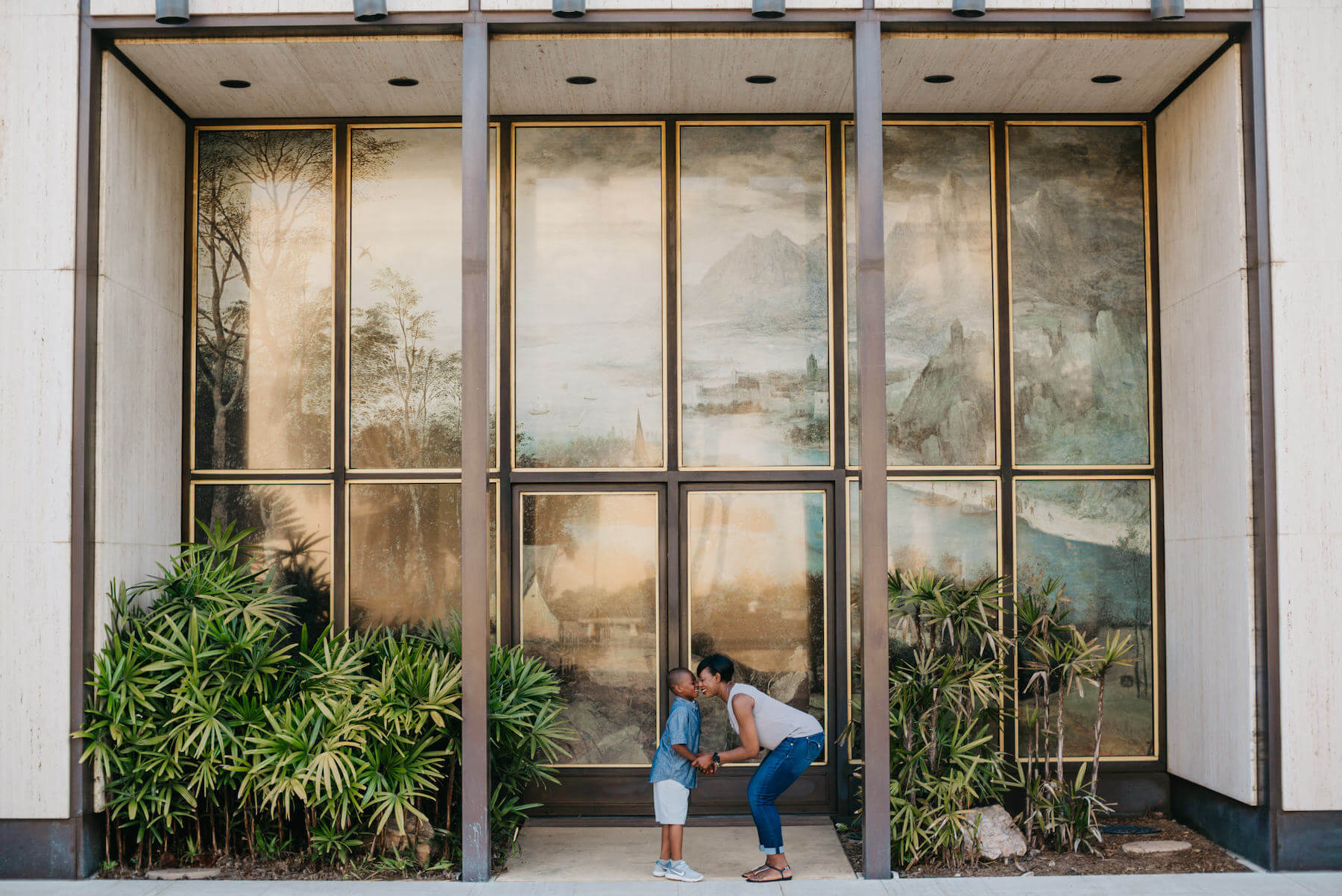 mother and son having fun, looking at each other in front of a large window in San Diego, California