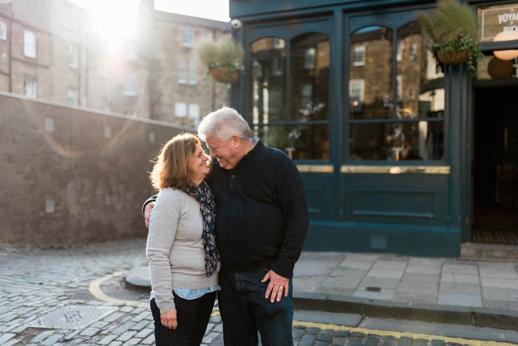 couple holding each other in front of a pub in Edinburgh, Scotland