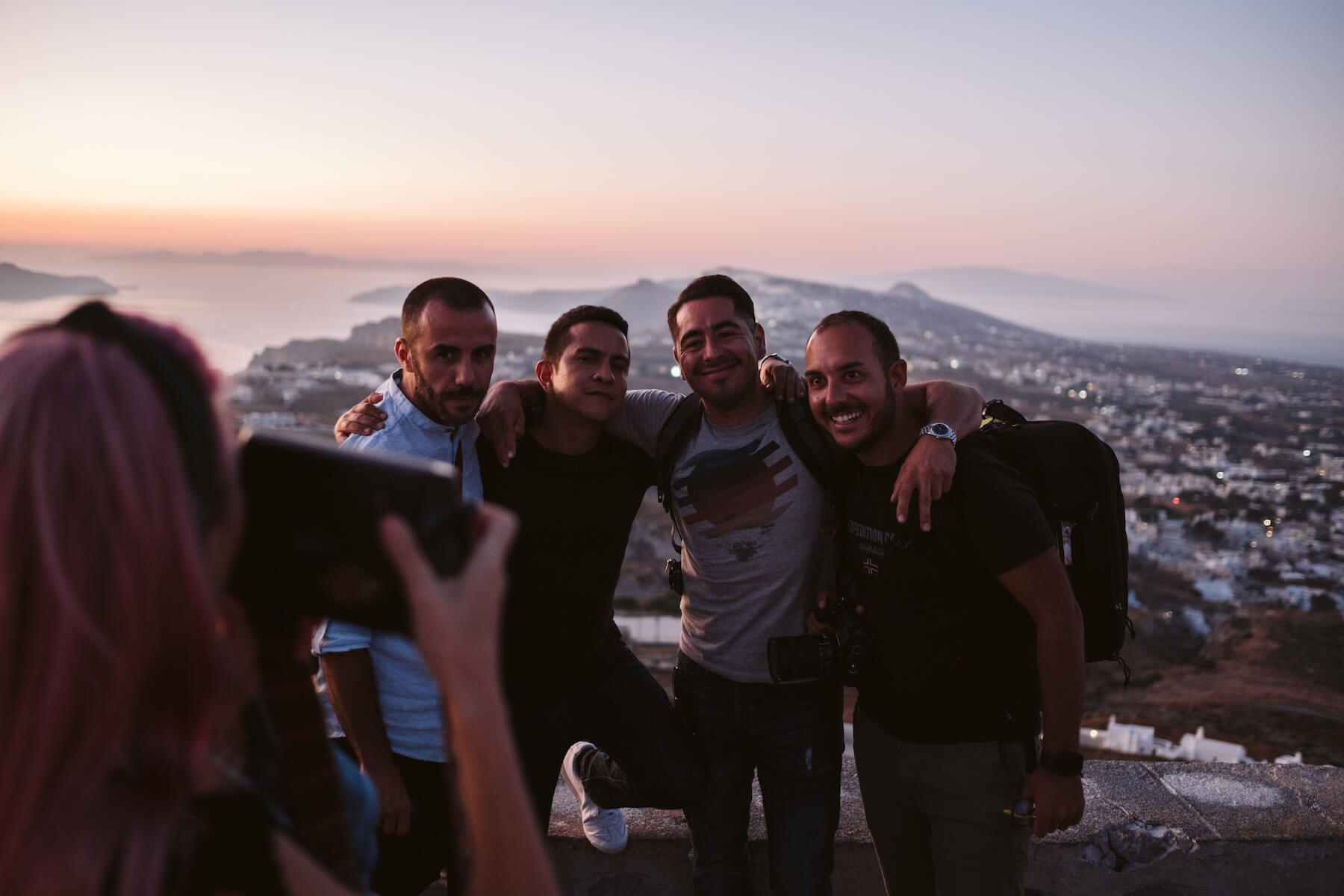 Group of men posing for a photo in front of the view in Santorini, Greece