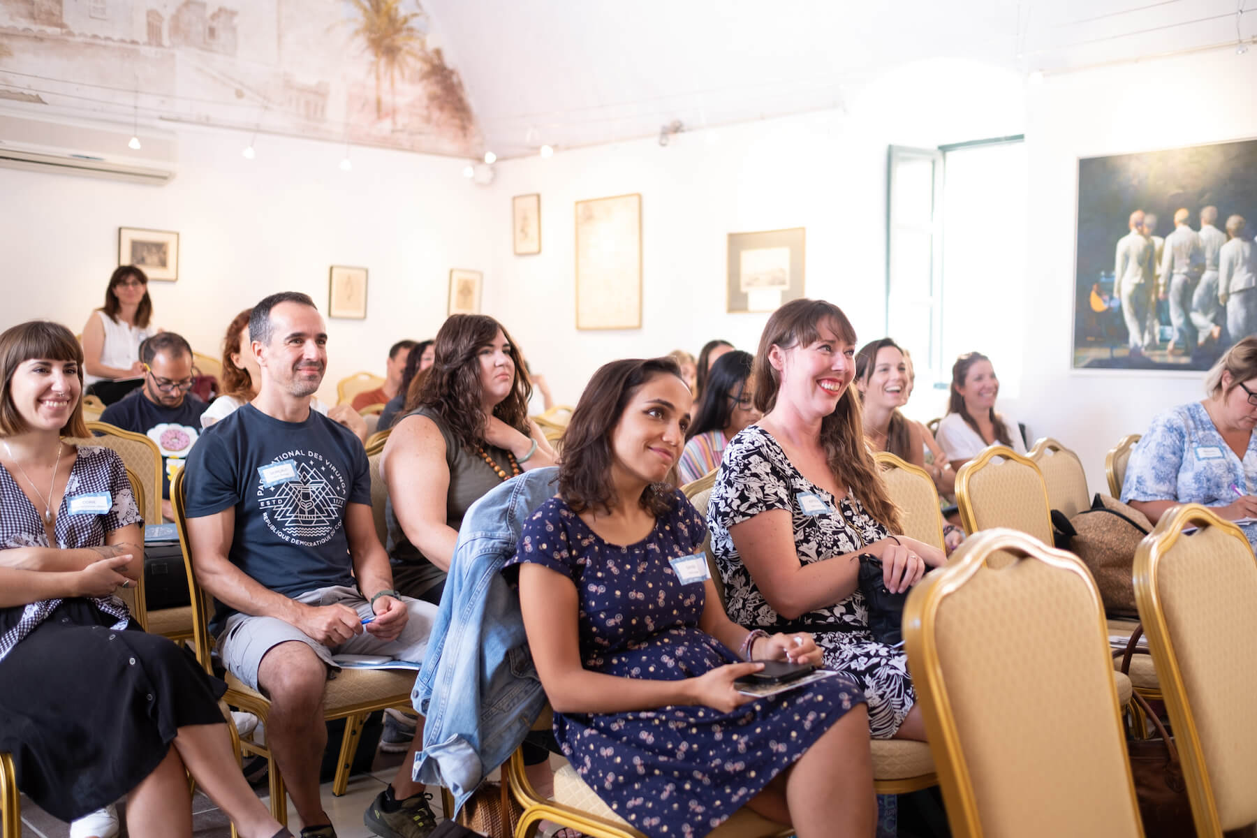 People listening to a speech in a conference room in Santorini, Greece