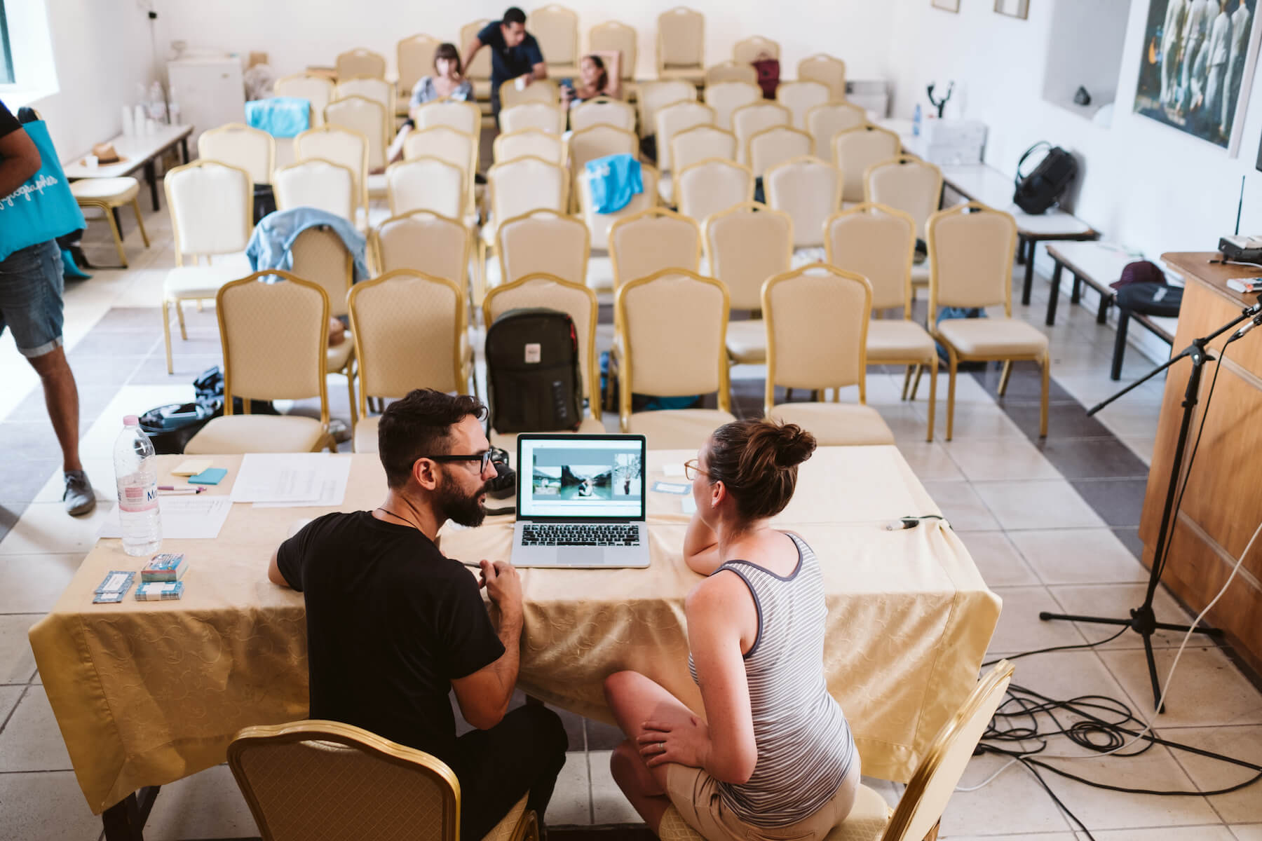 Two people talking around a laptop screen in a conference room in Santorini, Greece
