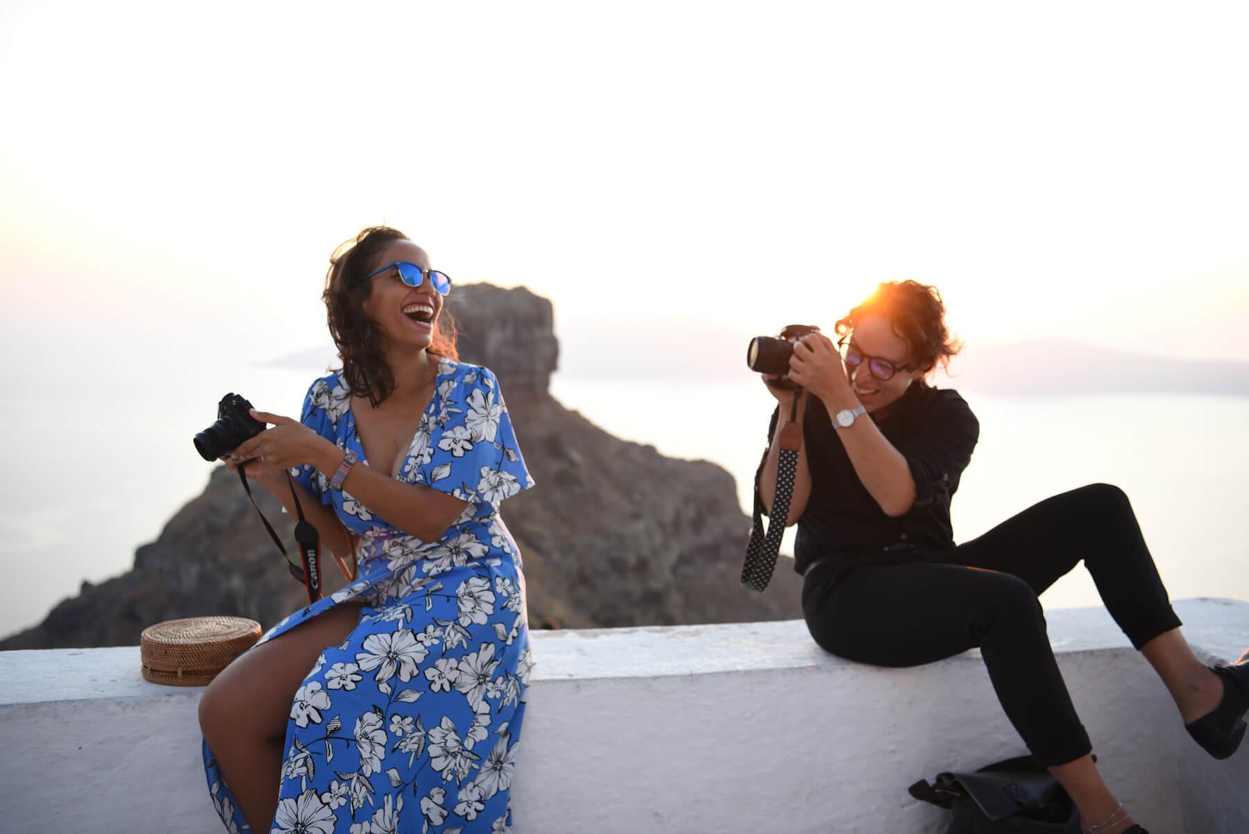 Two women sitting and laughing while one takes a photo in Santorini, Greece