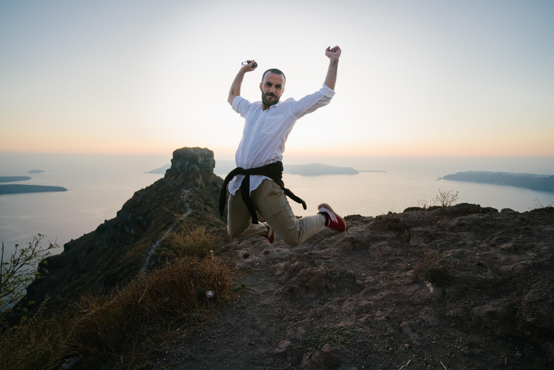 A man jumping for fun at Skaros Rock in Santorini, Greece