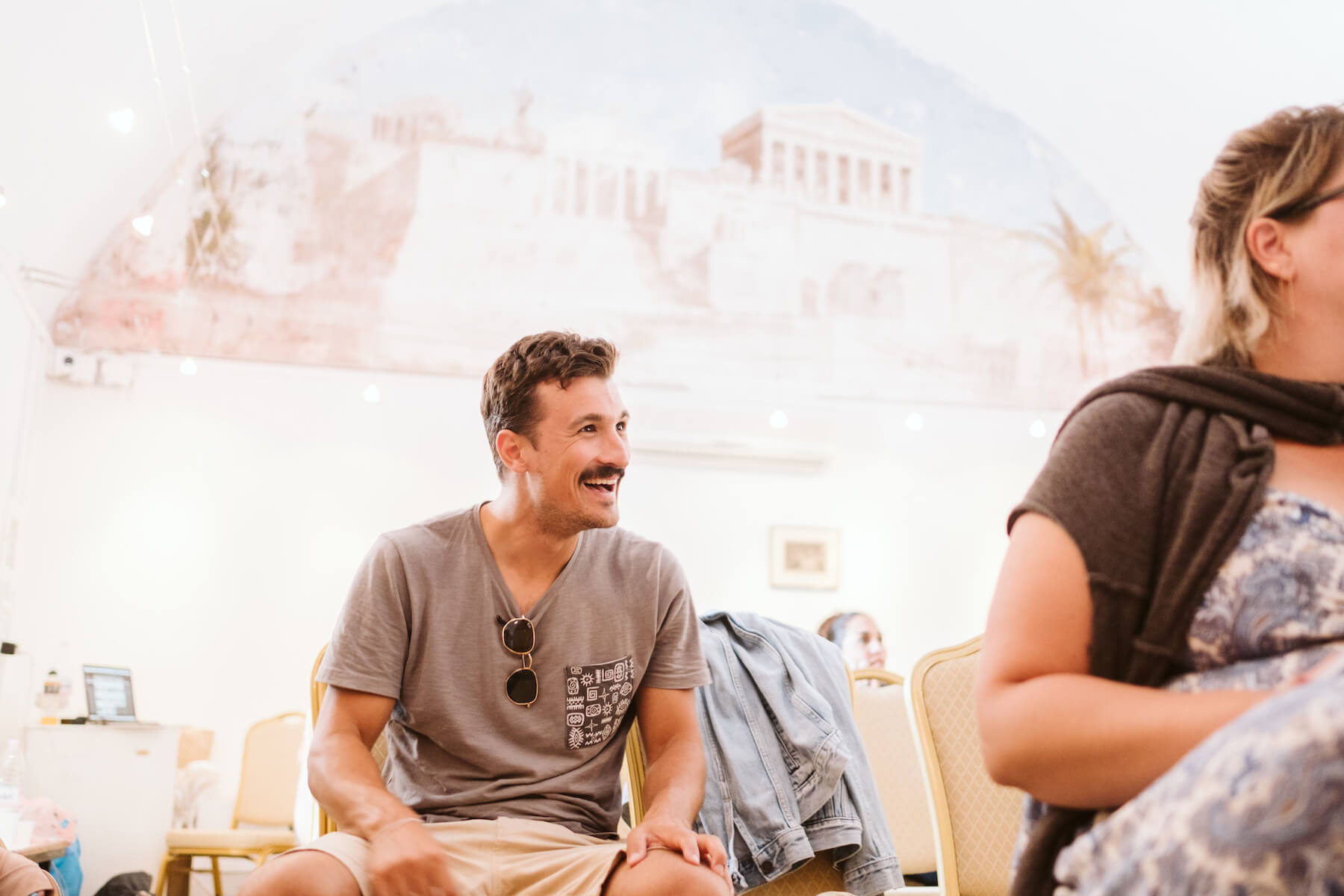 Man laughing while seated in a conference room in Santorini, Greece