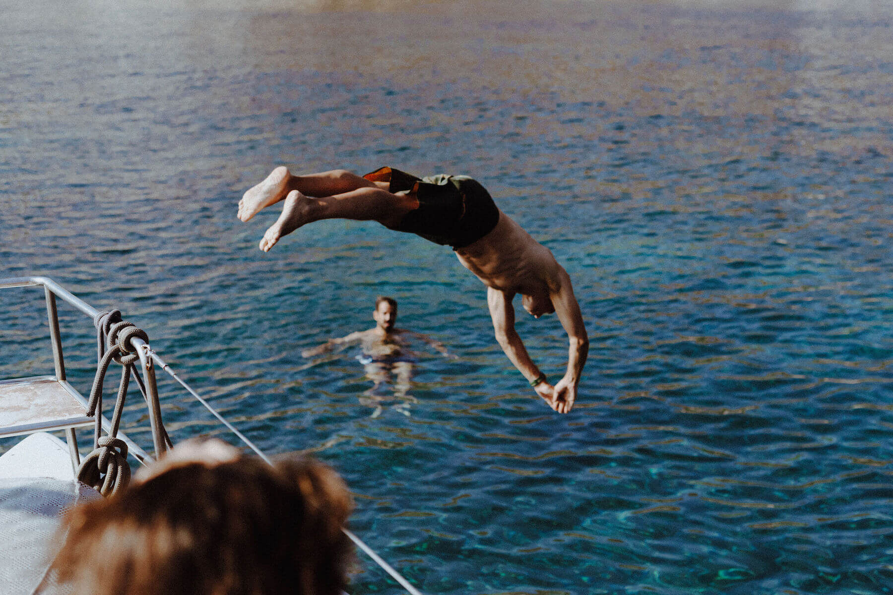 People diving off a boat in Santorini, Greece