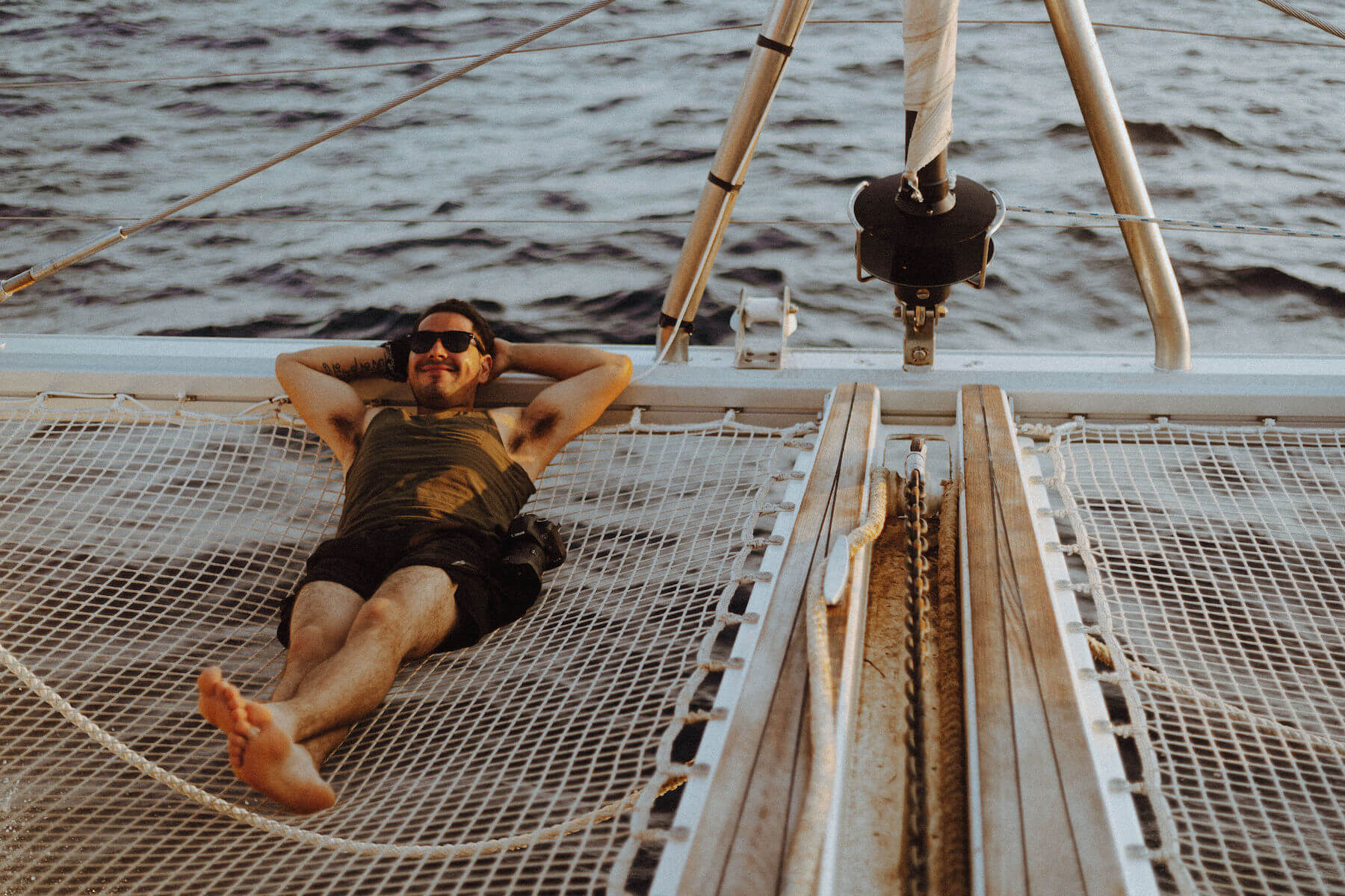Man smiling and lounging on a boat in Santorini, Greece