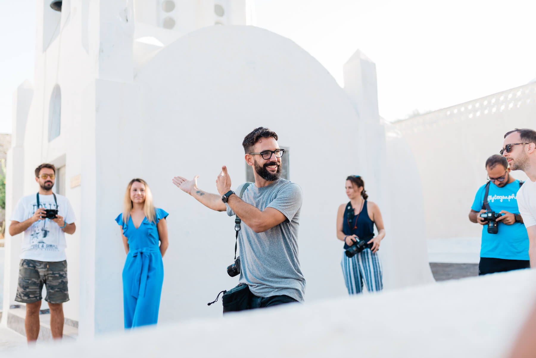 Photographer talking to group in front of church in Santorini, Greece
