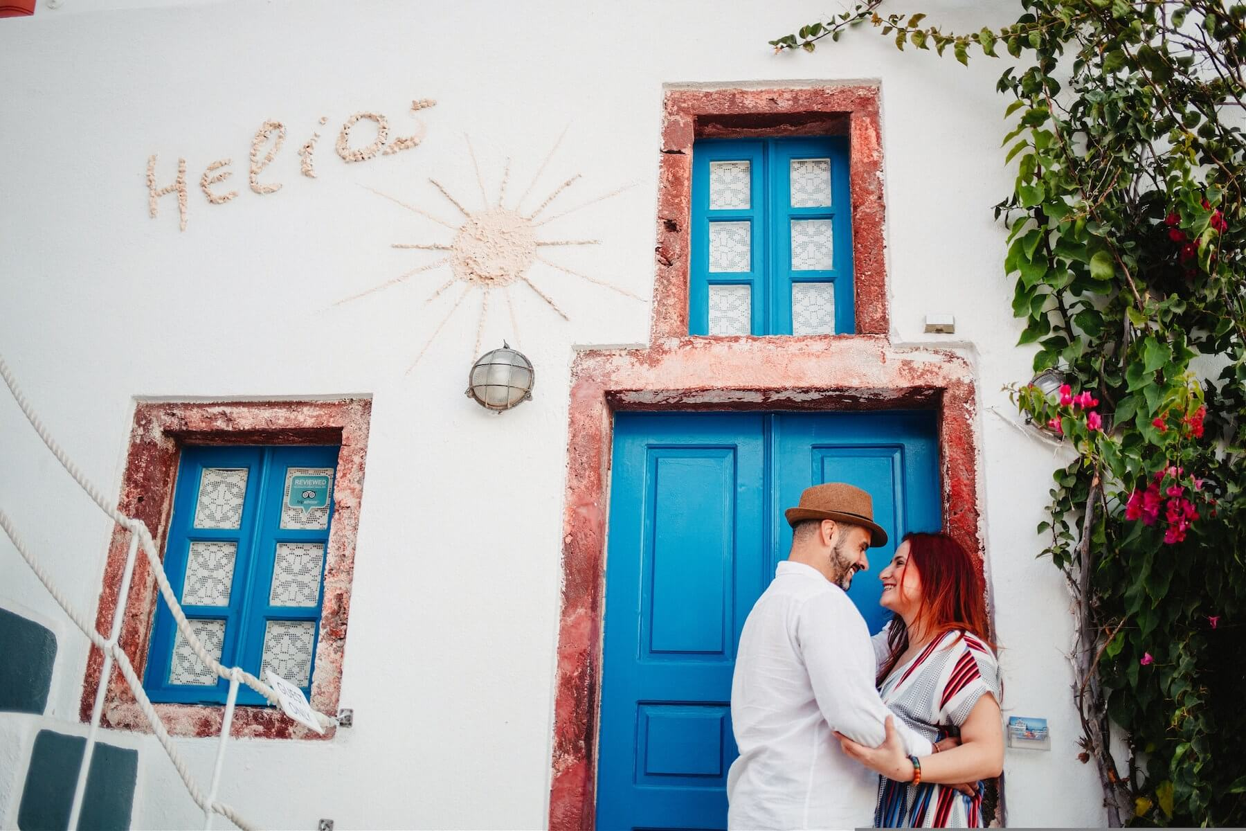 A couple embracing by a colourful wall in Santorini, Greece