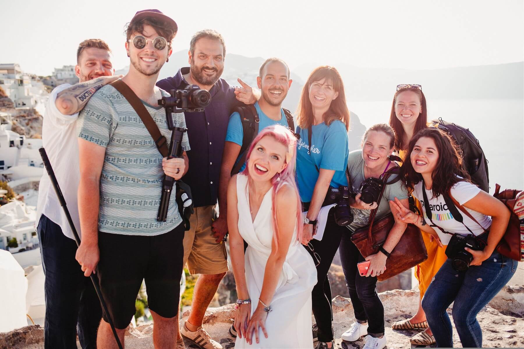 Group of people smiling and laughing in Santorini, Greece.
