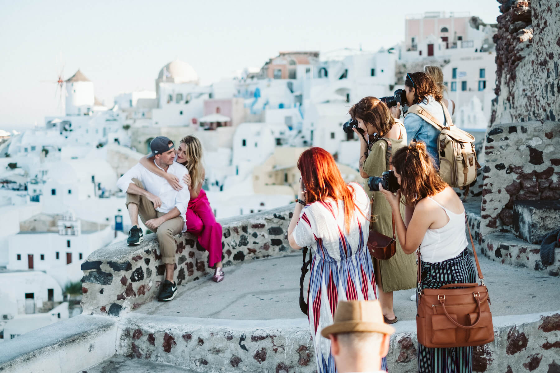 Photographers taking a photo of a couple in Santorini, Greece.