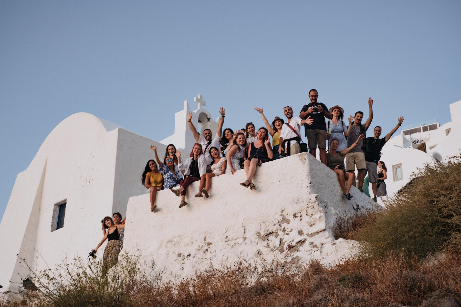 Photographers smiling and waving in a group in Santorini, Greece
