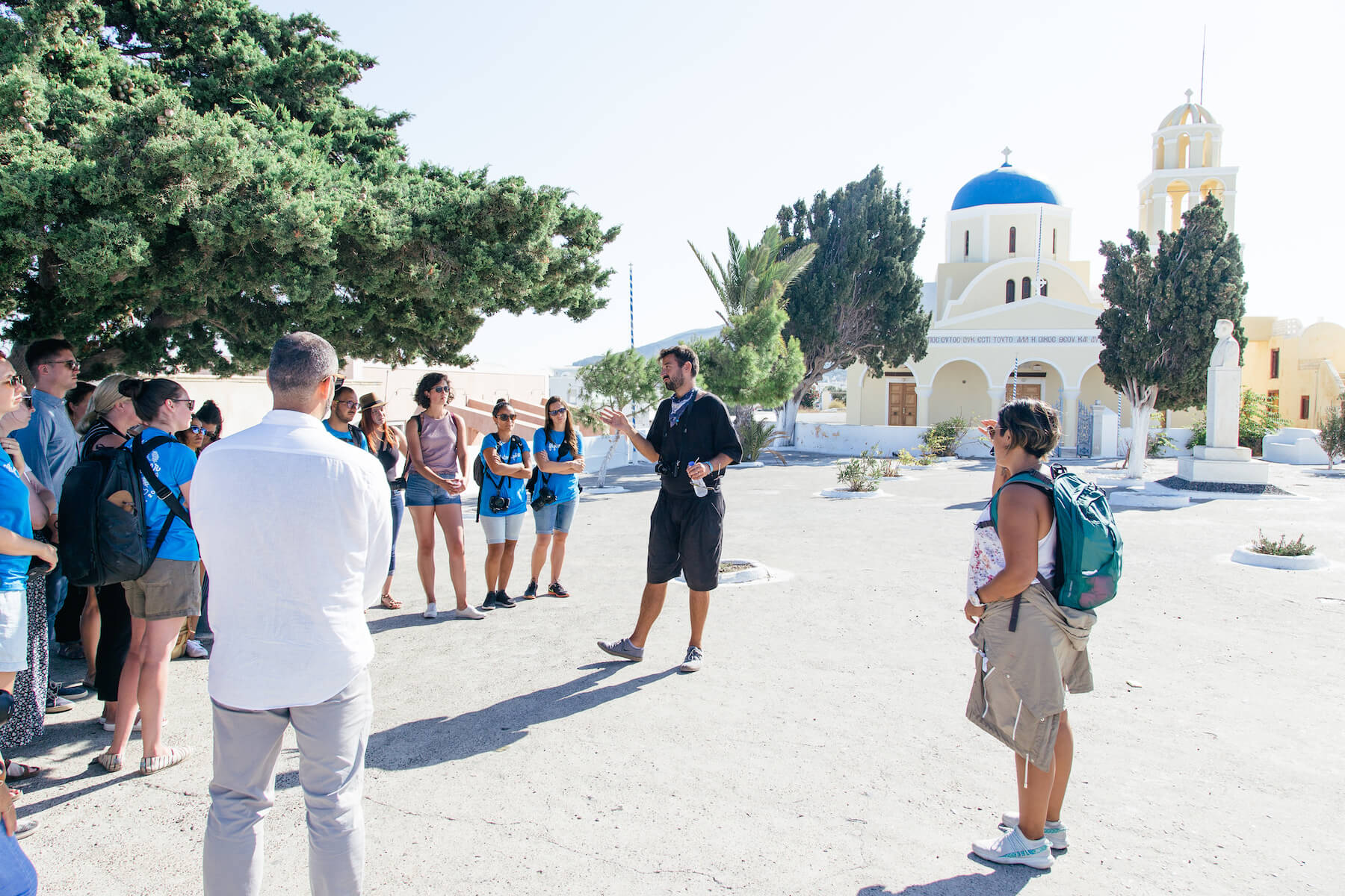Photographers in a group listening to a speaker in public square in Santorini, Greece.