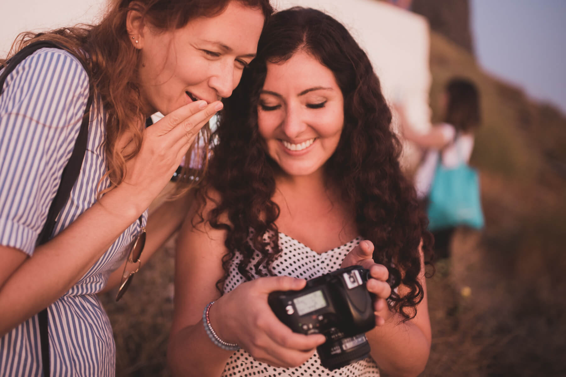 Two women looking at a back of a camera in Santorini, Greece