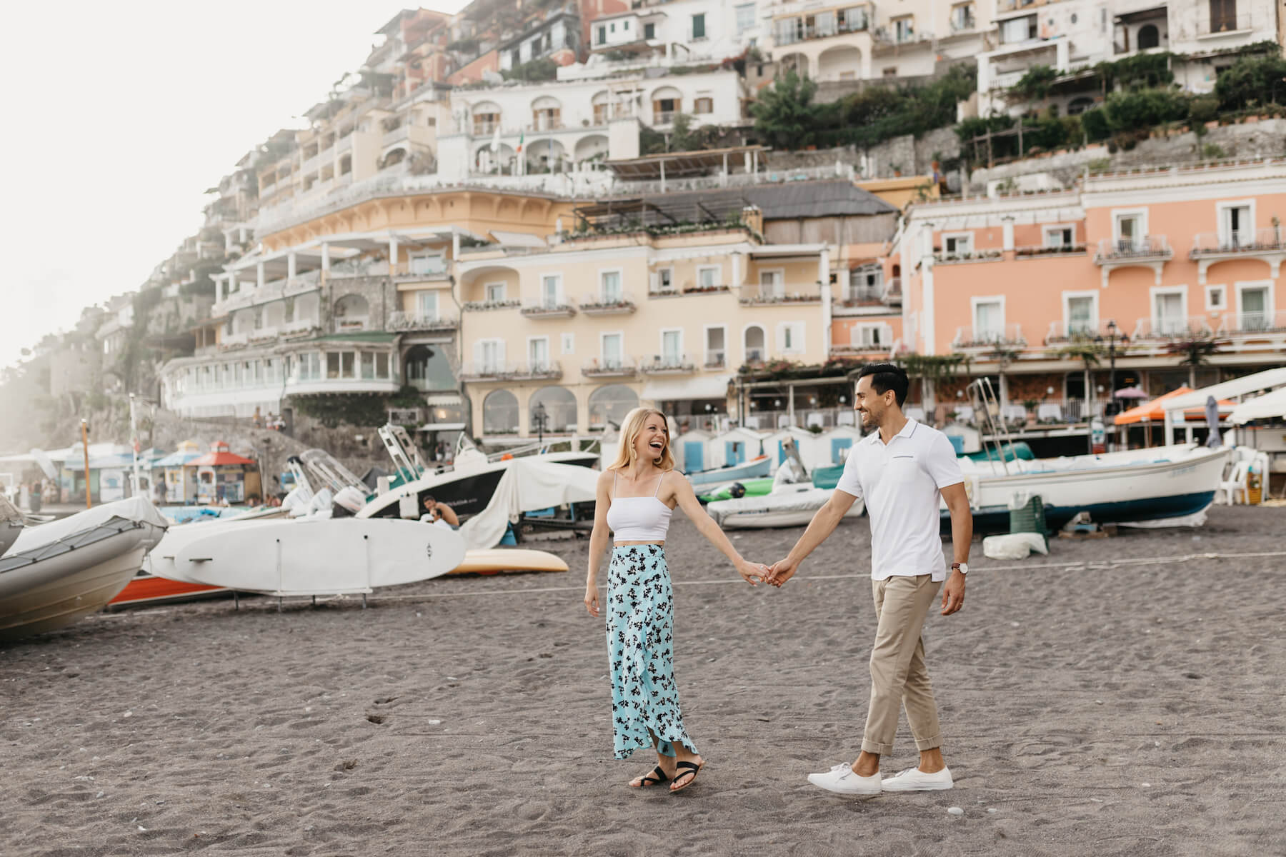 couple holding hands on the beach with the town of Positano behind them, in Positano, Italy