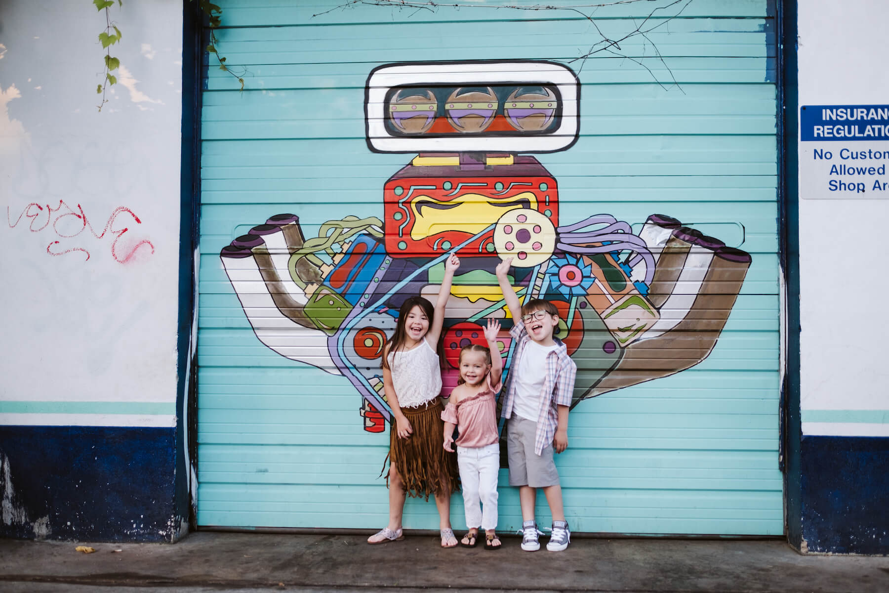 Kids in front of graffiti having fun and holding that arms up in the air in Austin, Texas