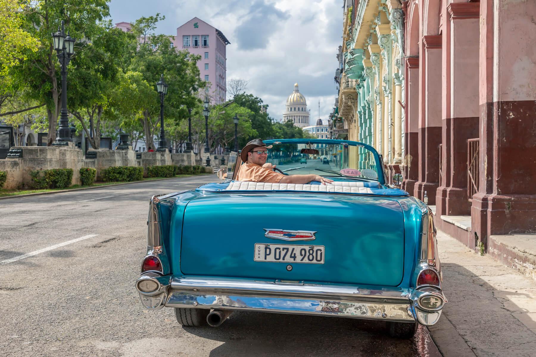 solo traveller sitting in a vintage car in Havana, Cuba