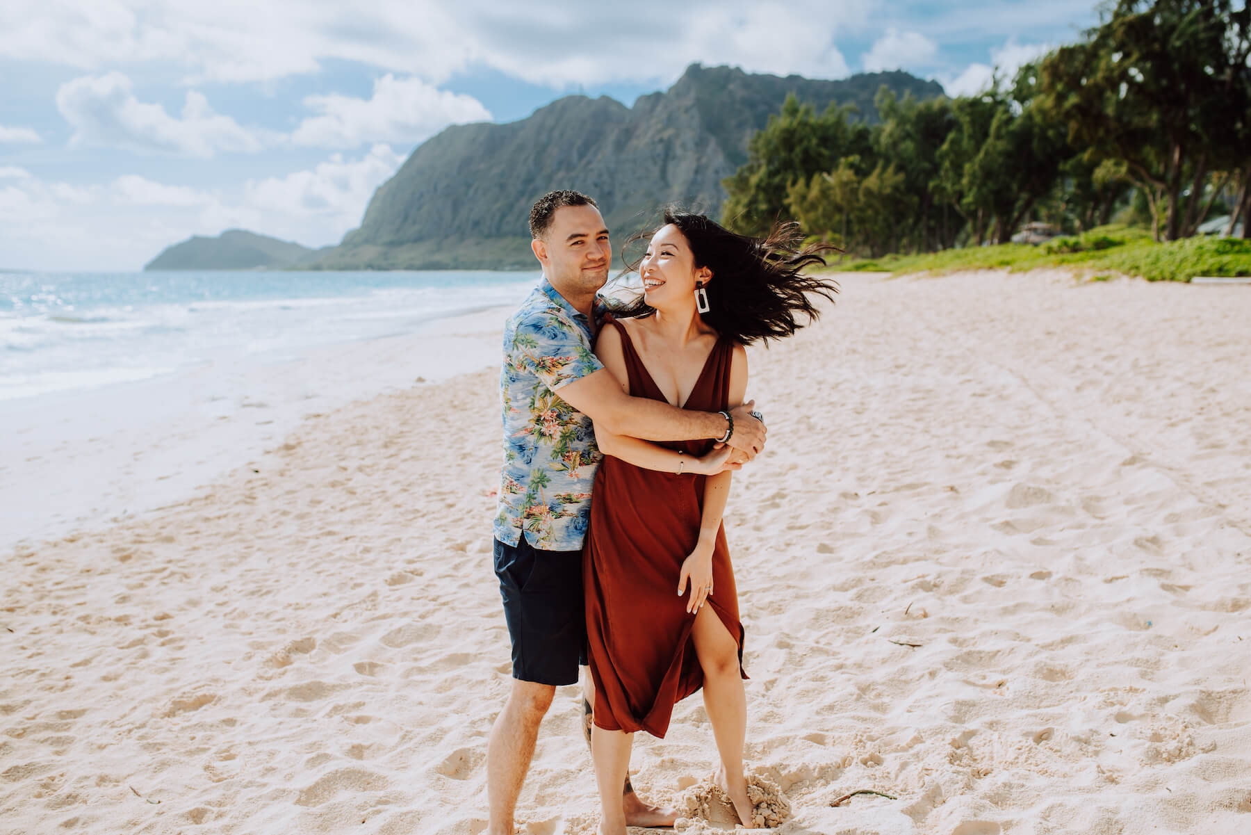 Couple embracing and being playful on the beach in Honolulu, Hawaii