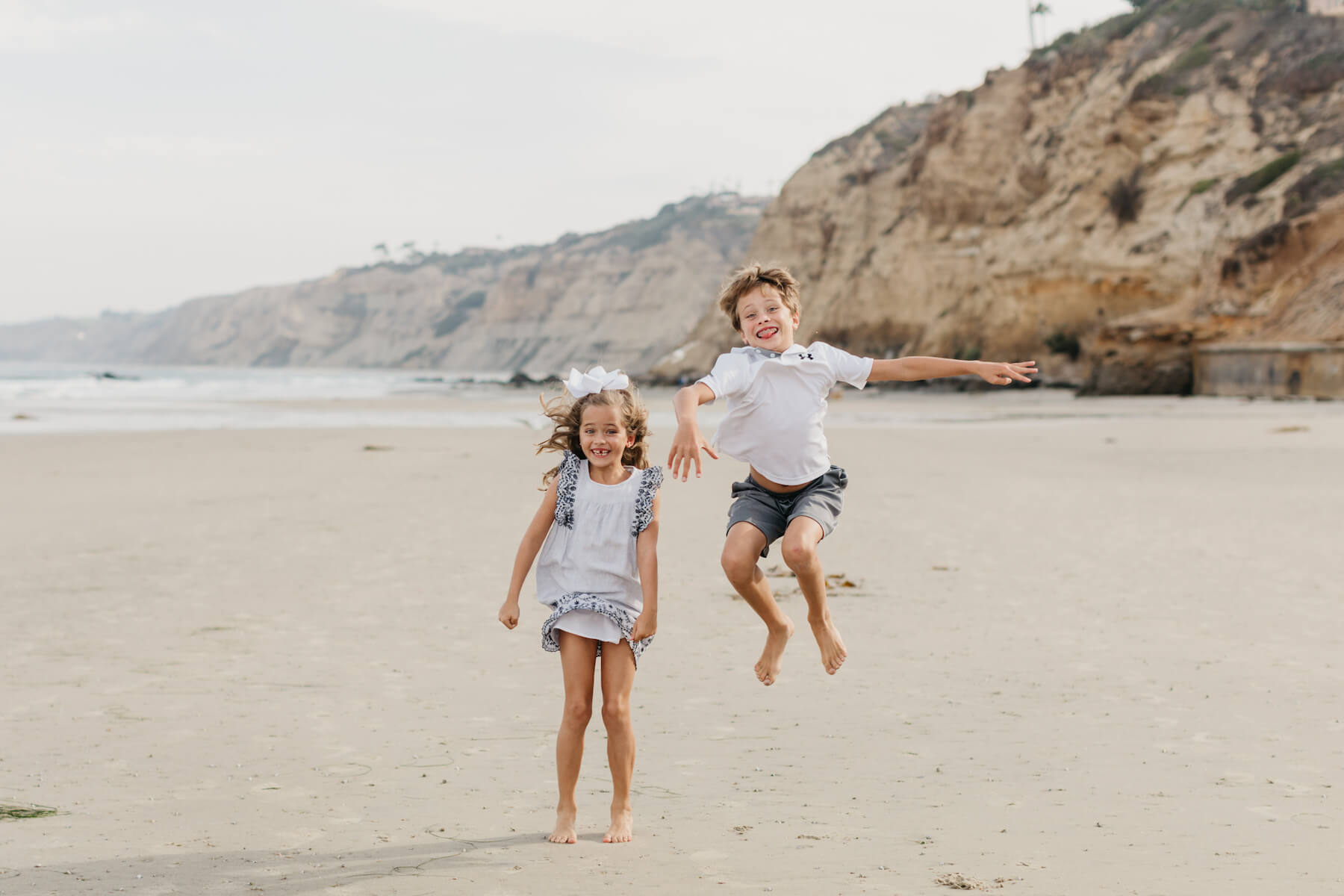 brother and sister on the beach, jumping in San Diego, California