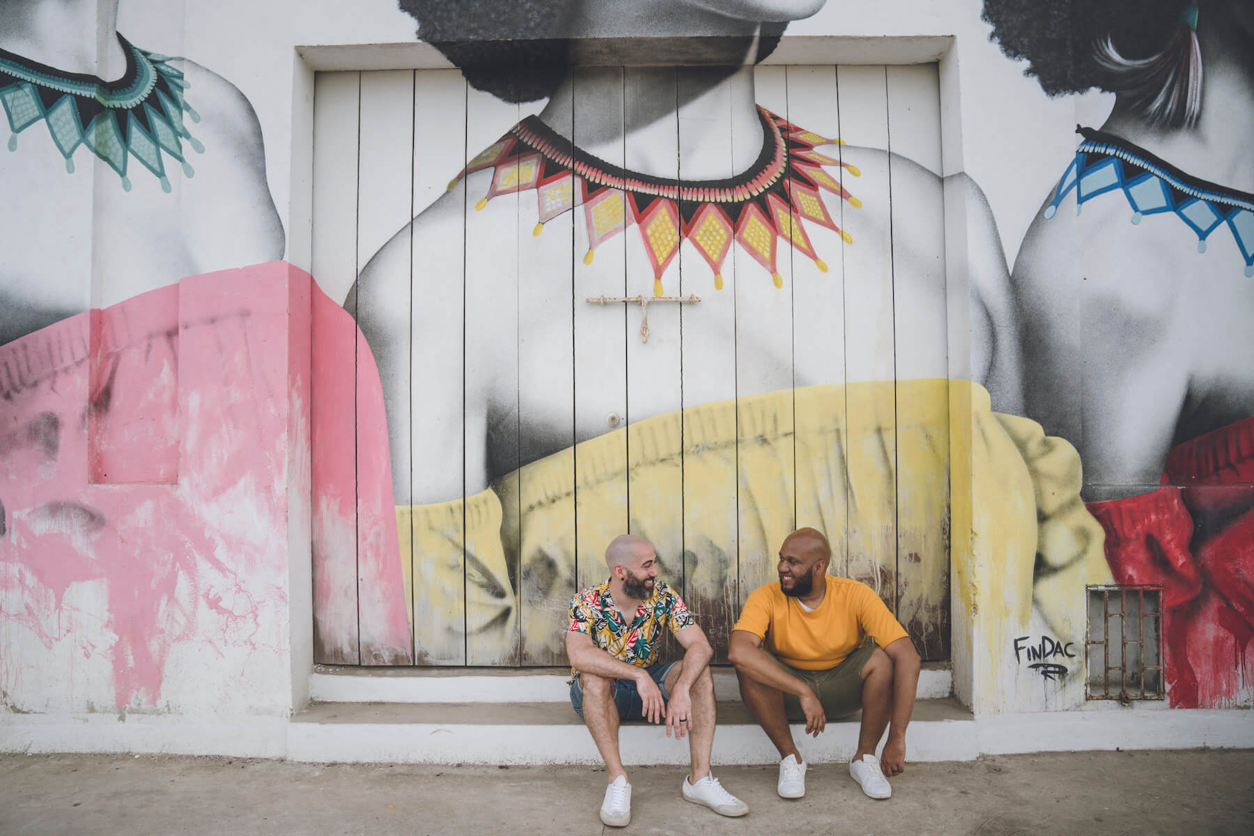 a LGBTQ couple sitting in front of a colourful wall in Cartagena, Columbia