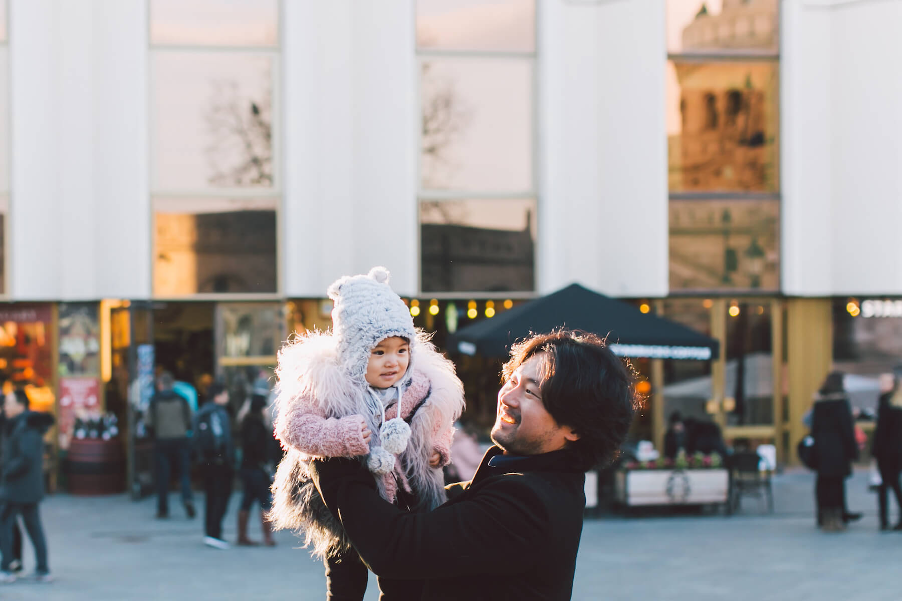 father holding a baby girl up in the air in a city square in Budapest, Hungary