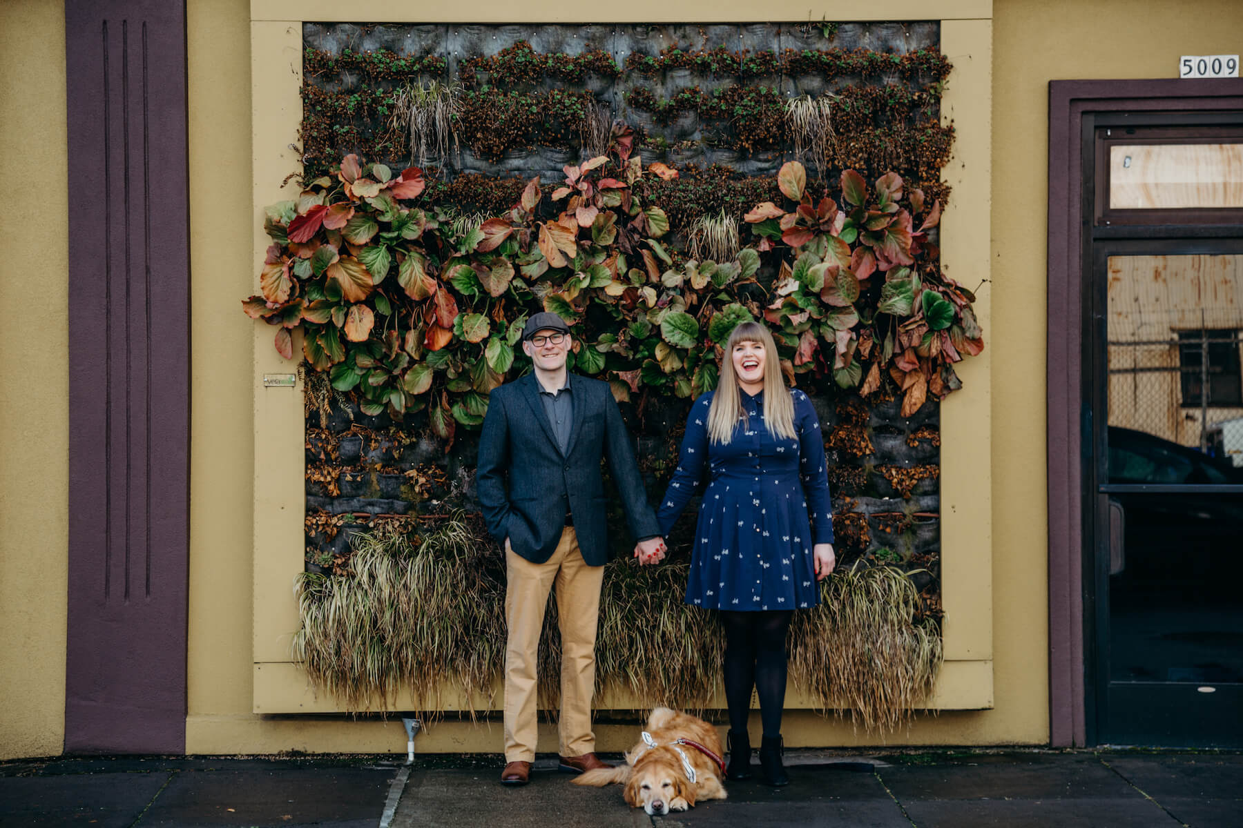 couple with a dog standing in front of a building in portland, Oregon