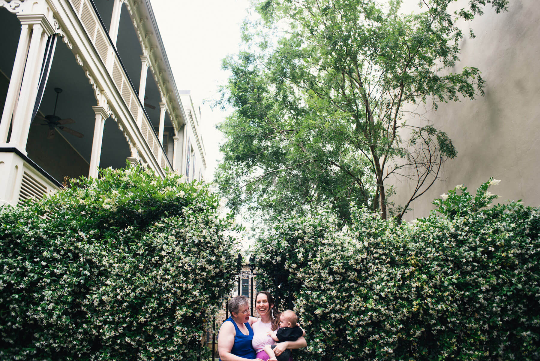 a LGBTQ Couple with their child in front of a historic building in Savannah, Georgia, United States of America