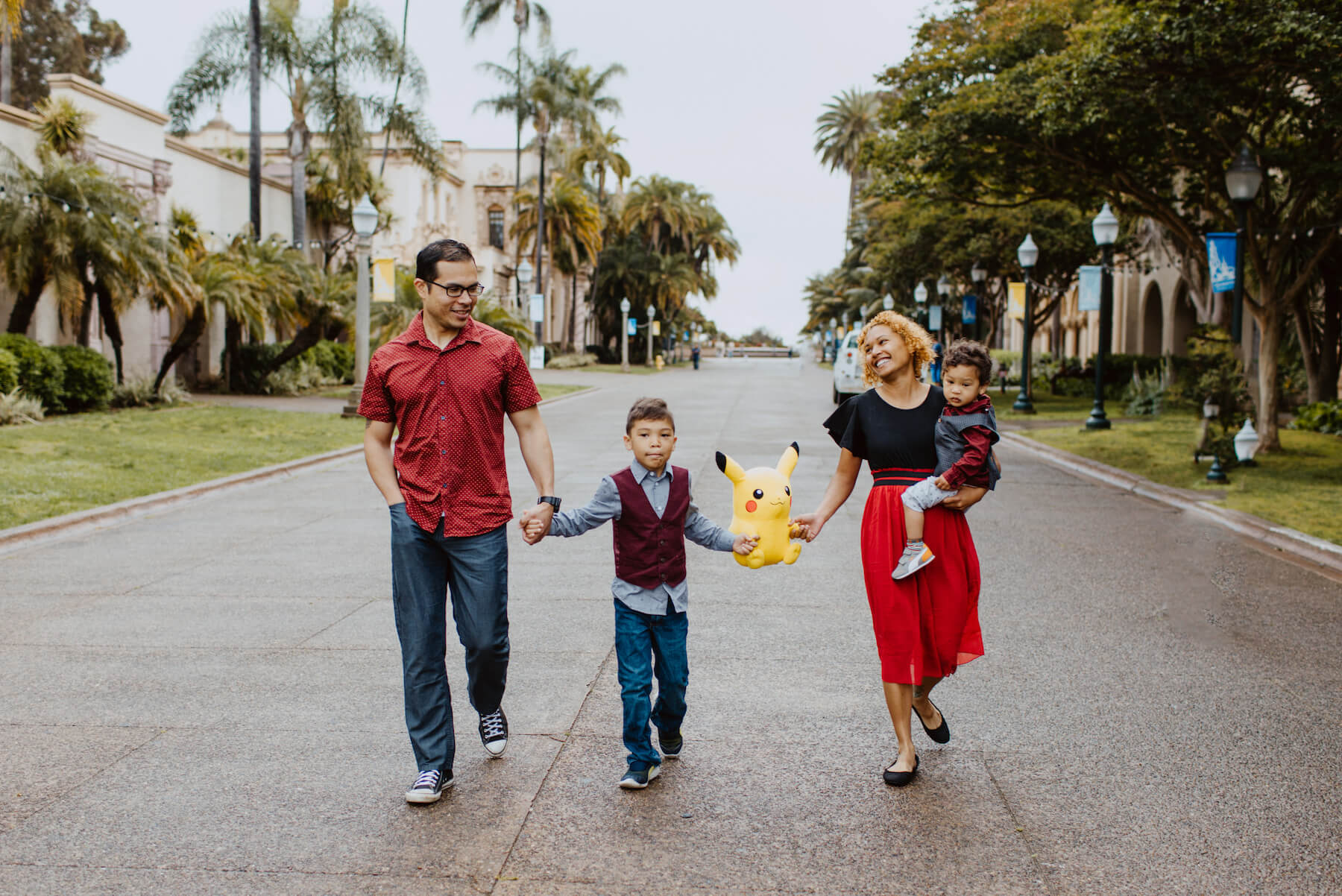 a family holding hands and walking down the street in San Diego, California
