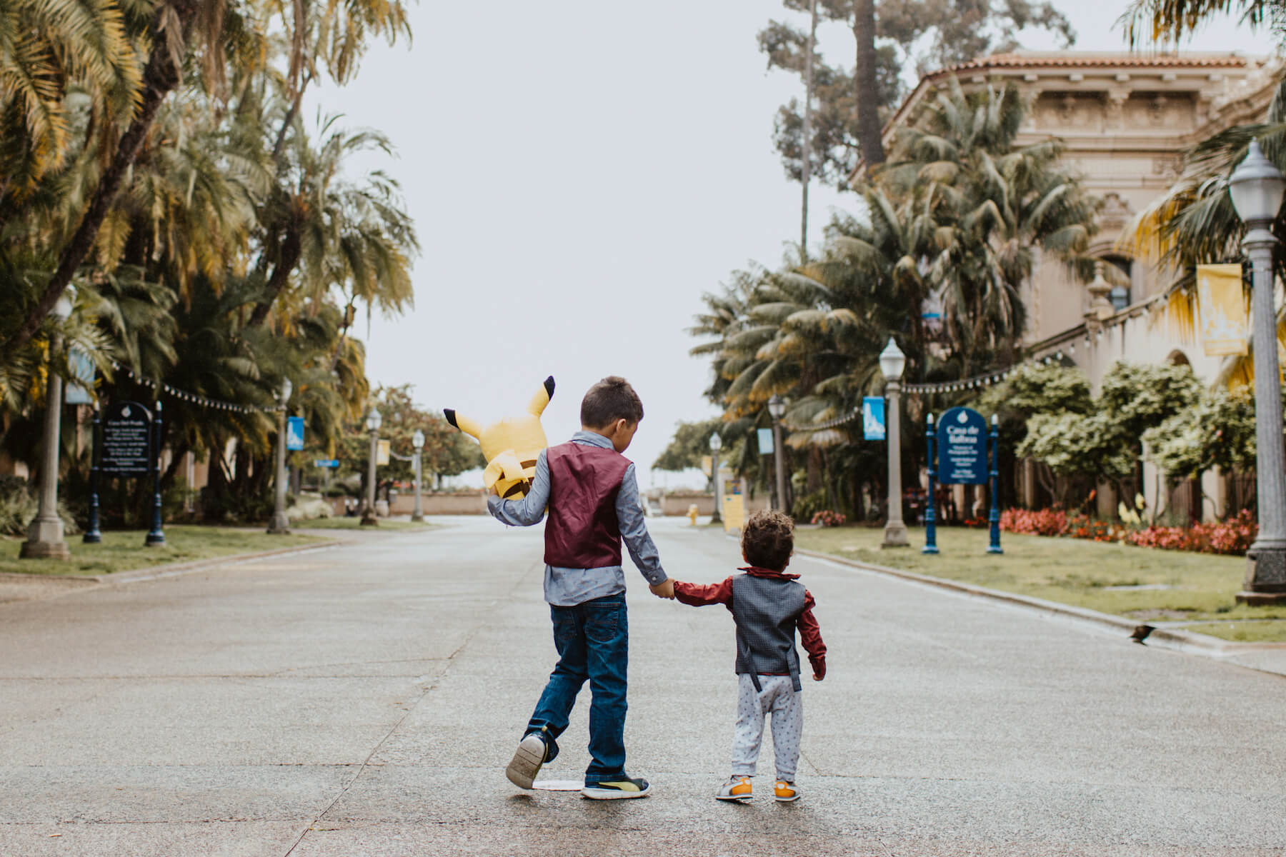 two brothers holding hands, walking in San Diego, California