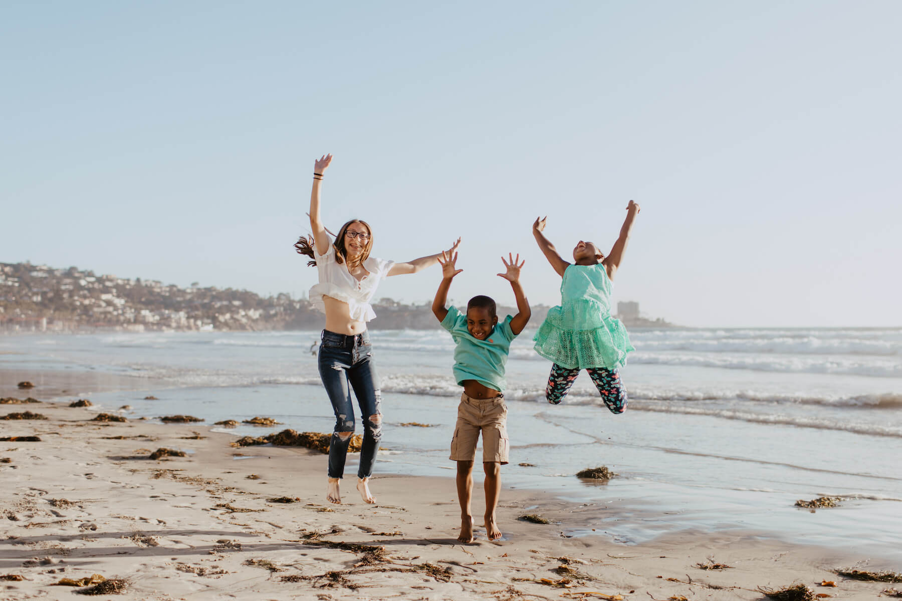 3 kids jumping on the beach in San Diego, California