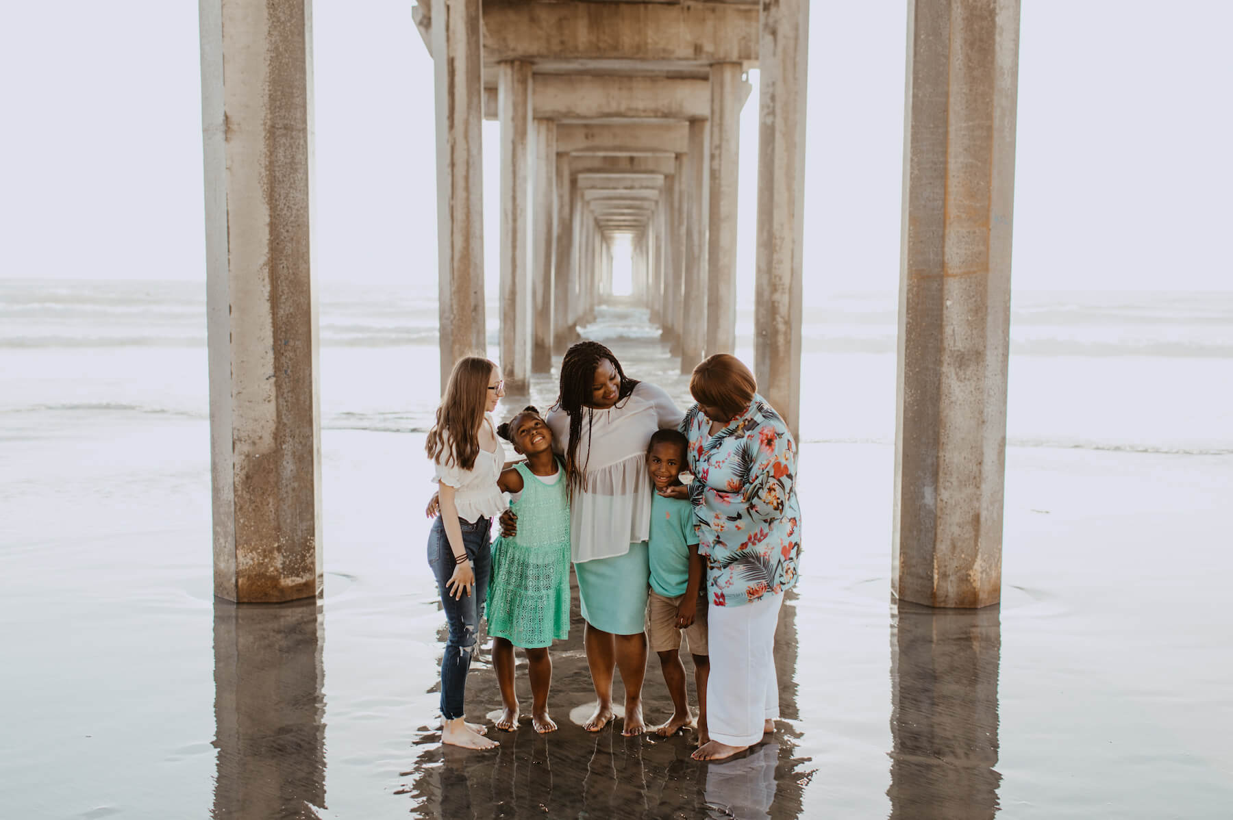 A family standing under the boardwalk on the beach in San Diego, California