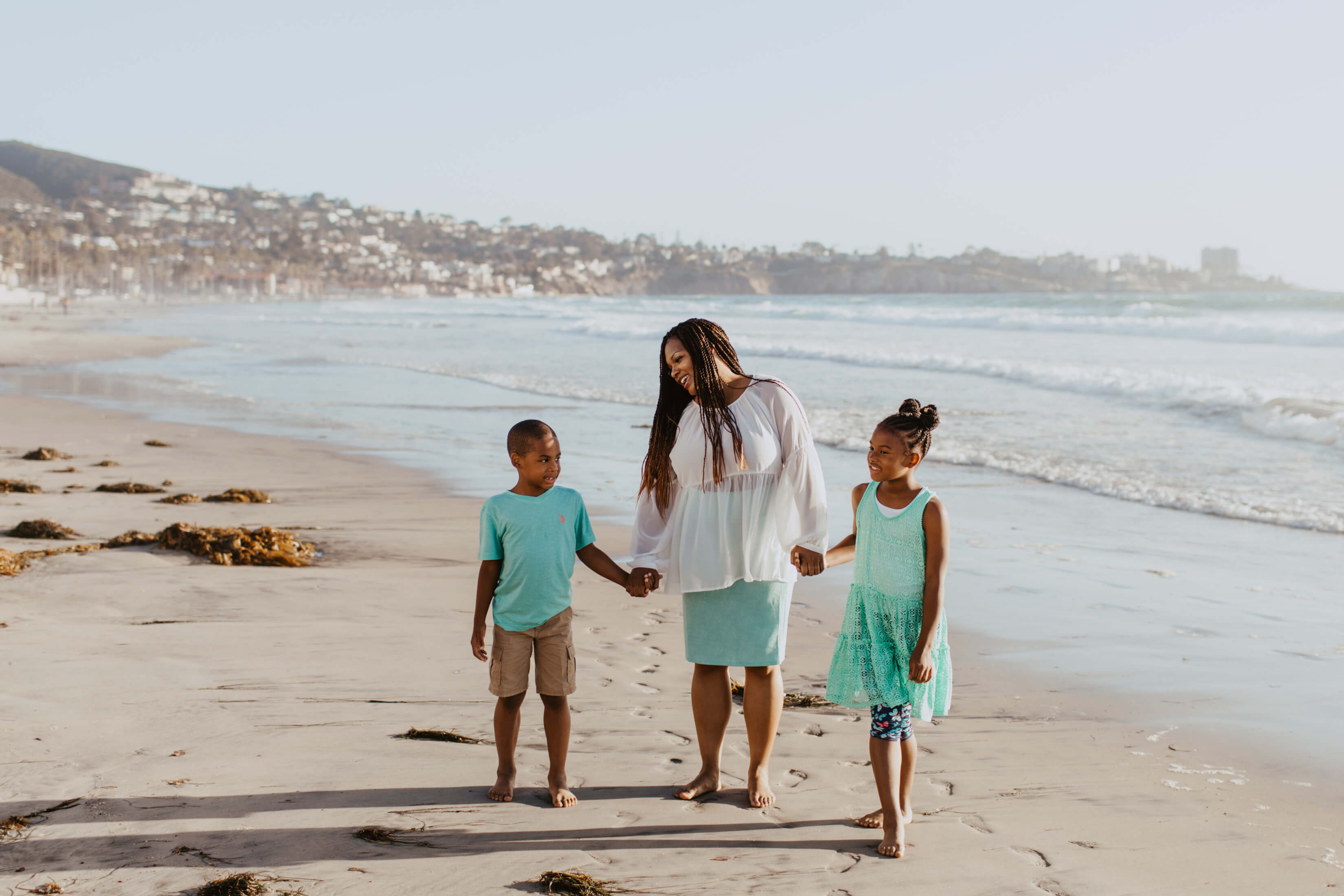 mother with son and daughter holding hands on the beach in San Diego, California